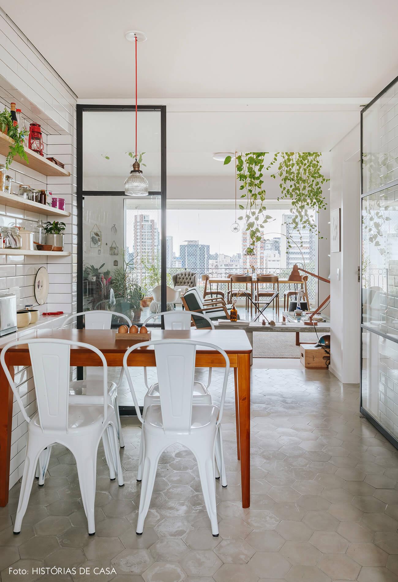 Cozinha integrada com portas de serralheria e vidro, cadeiras Tolix