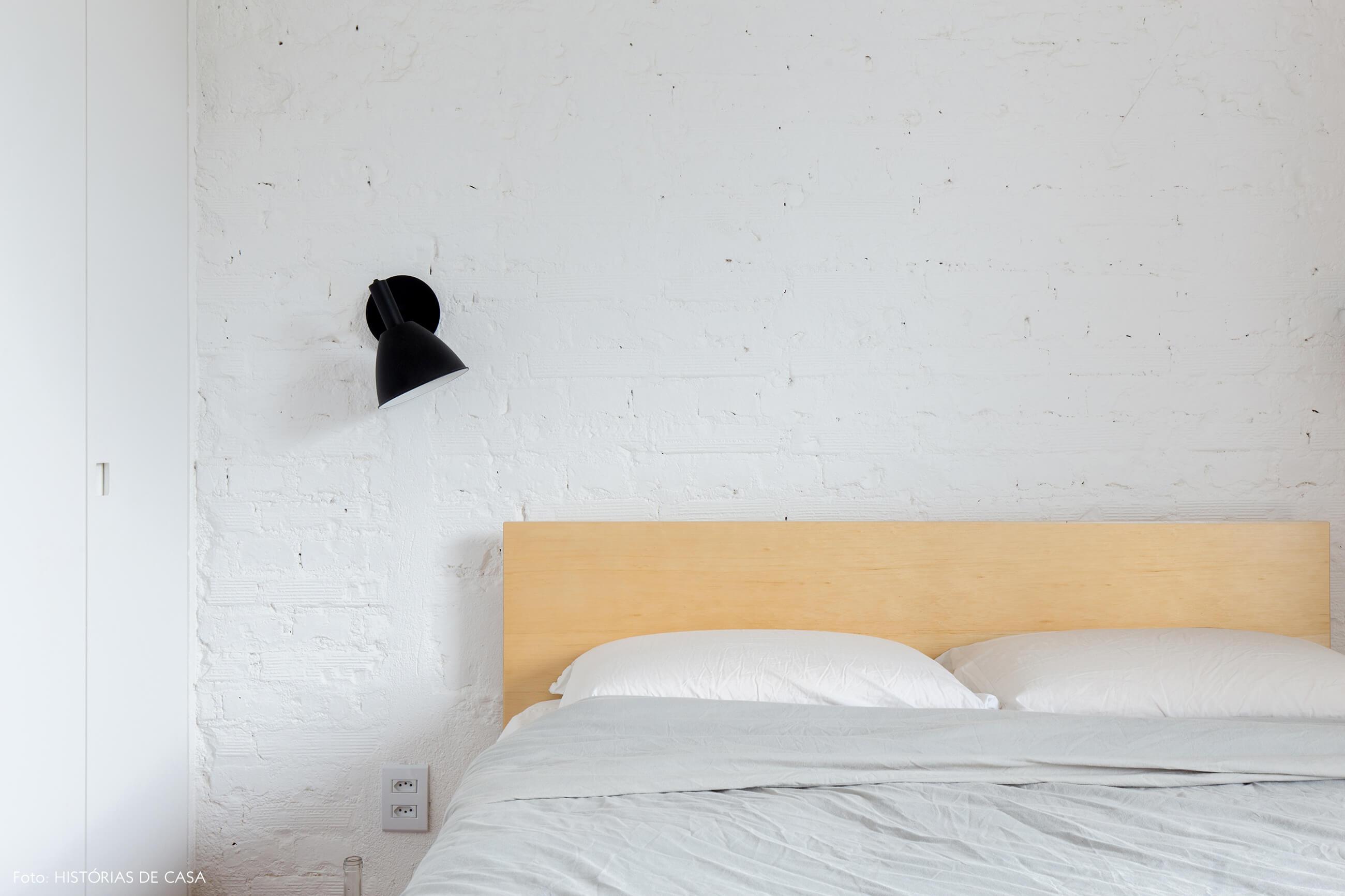 Quarto com parede de tijolinho branco e cama de madeira clara