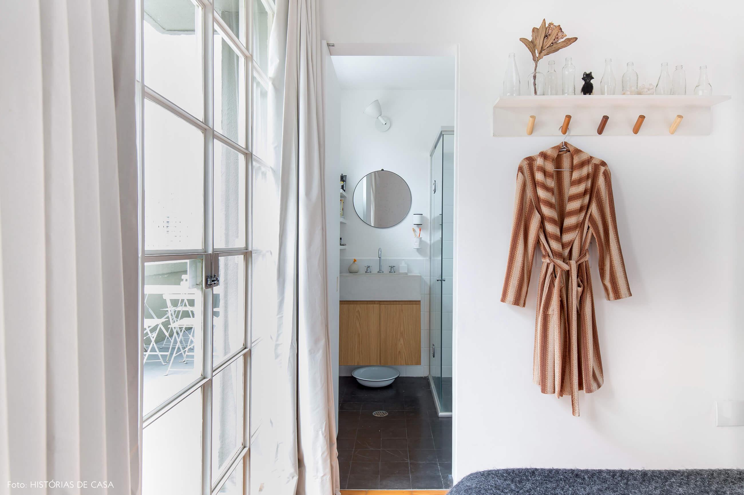 Quarto com cabideiro de madeira e banheiro de estilo industrial