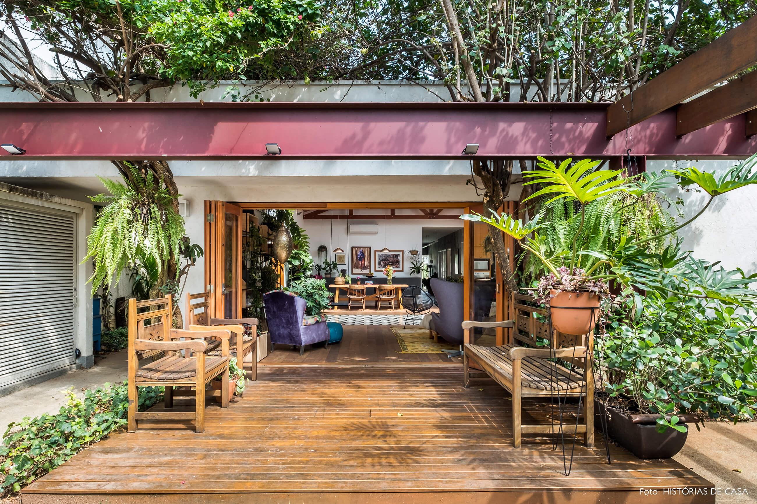 Casa com jardim. Deck de madeira na entrada e sala integrada.