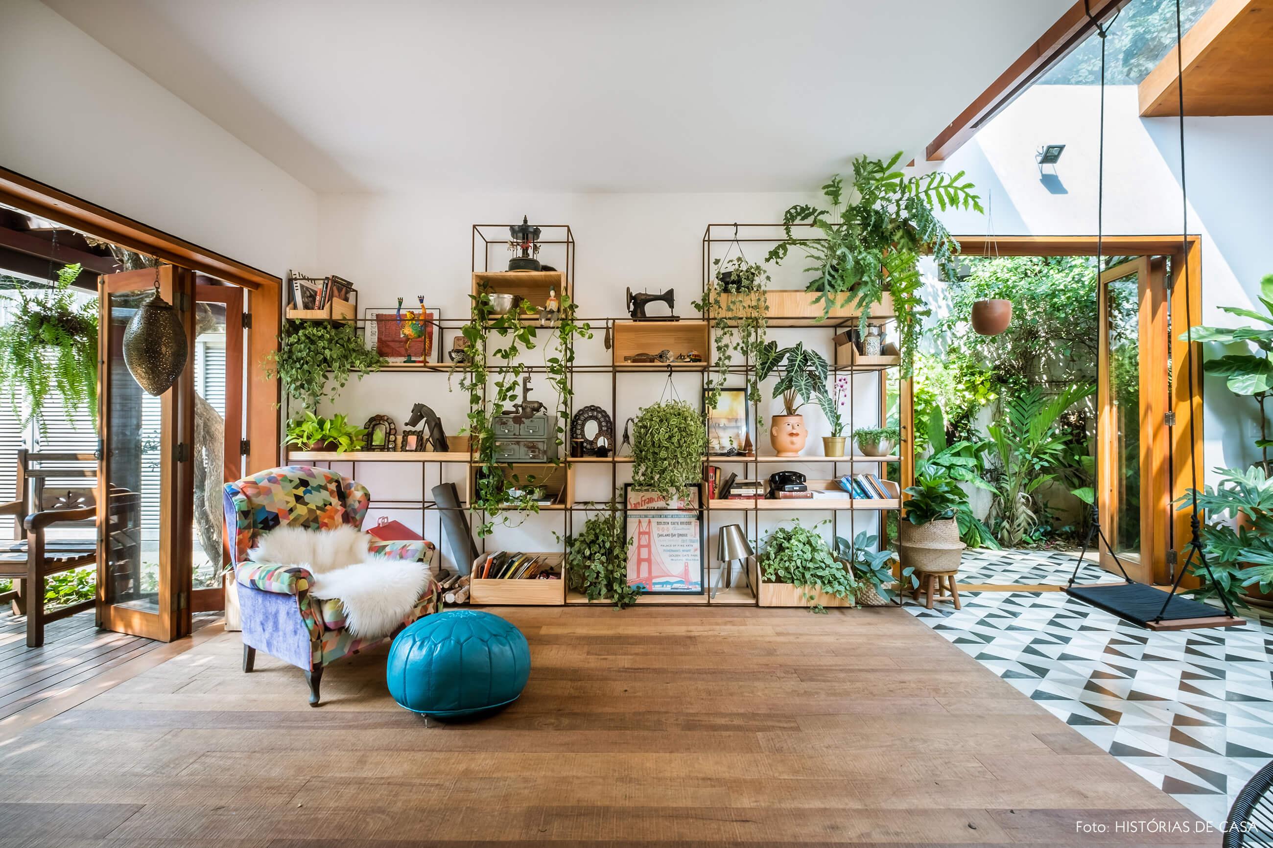 Sala integrada, estante com muitas plantas e piso de madeira de demolição.