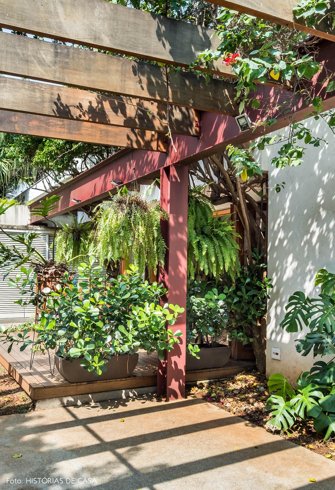 Casa com jardim. Vigas coloridas e plantas penduradas.