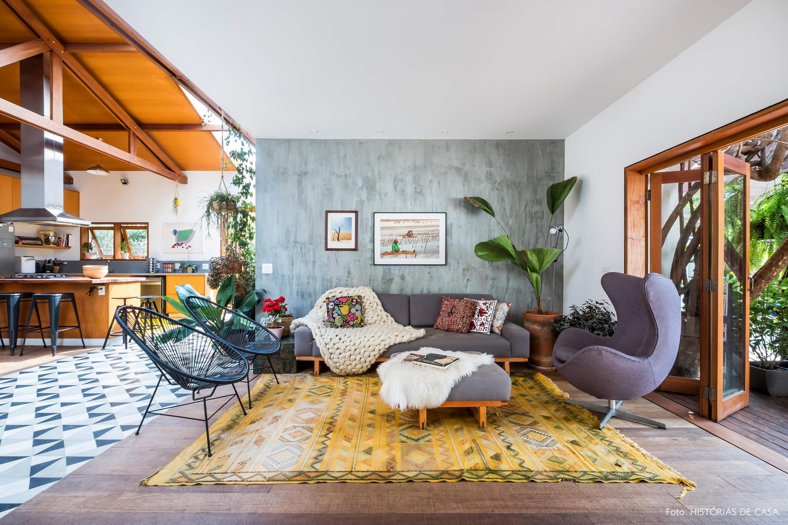 Sala com tapete colorido e parede de cimento queimado atrás do sofá.