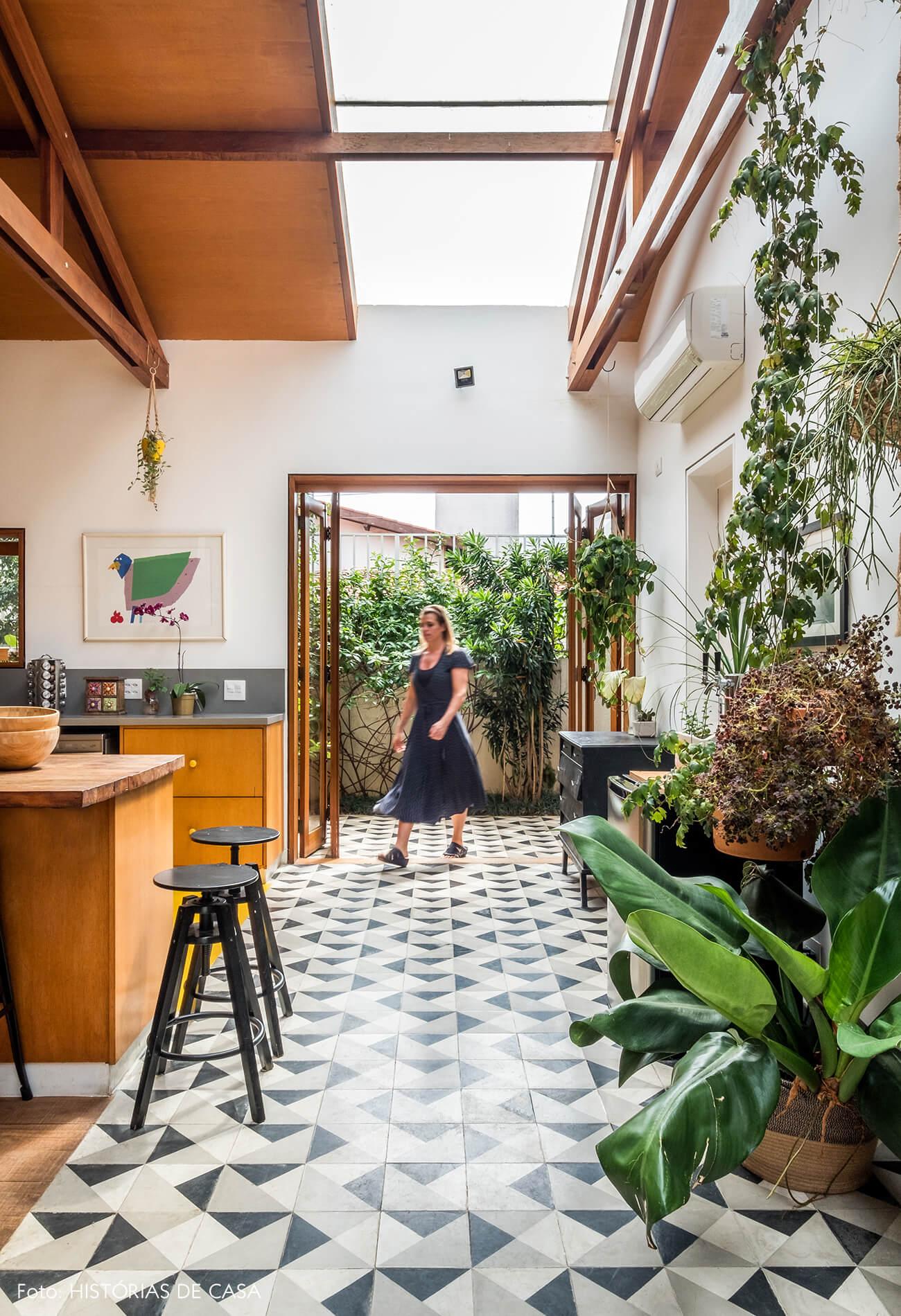 Cozinha com pé-direito alto e faixa de ladrilhos hidráulicos no piso
