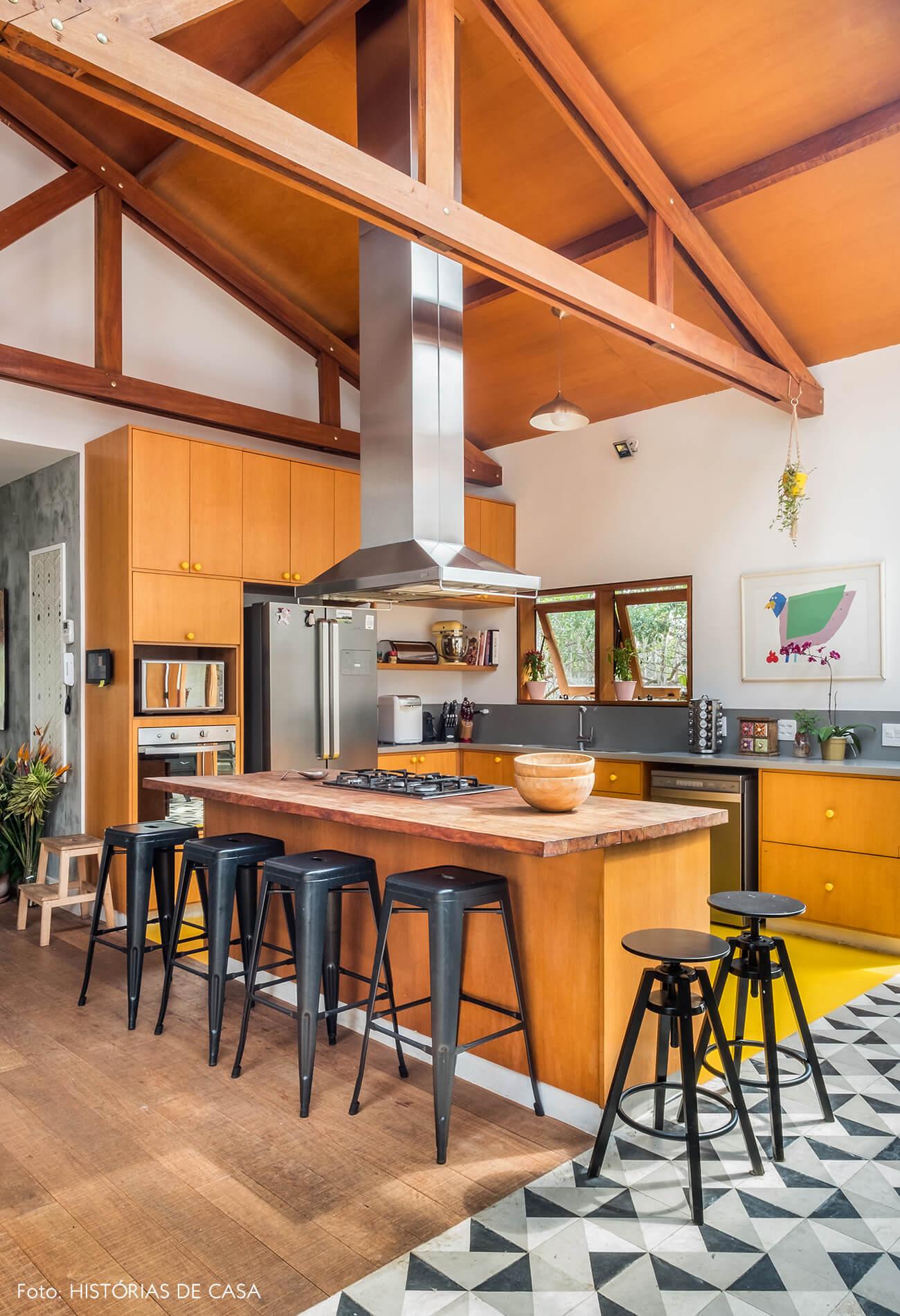 Cozinha com ilha central e faixa de ladrilhos hidráulicos no piso