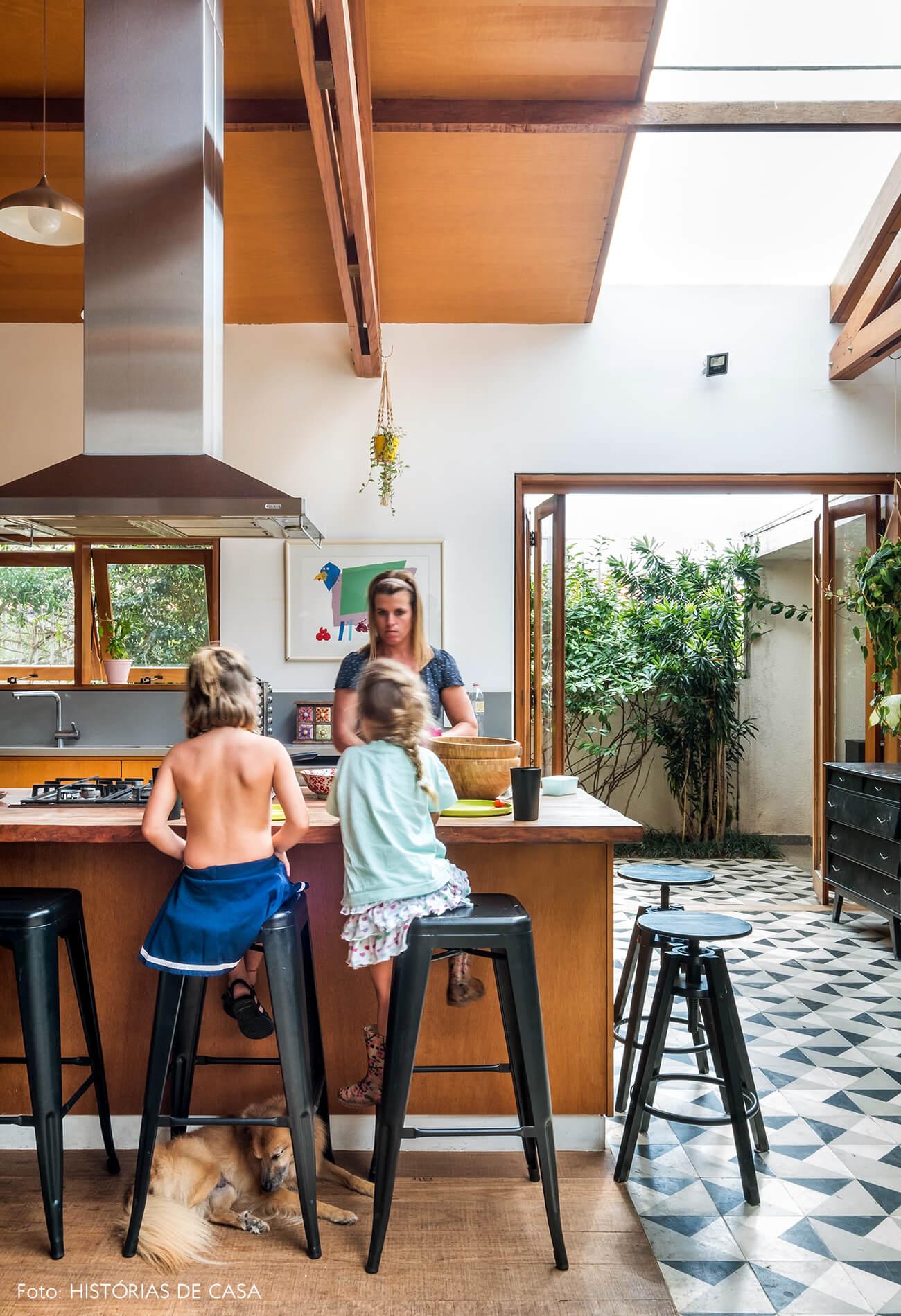 Cozinha com ilha central e banquetas pretas de metal