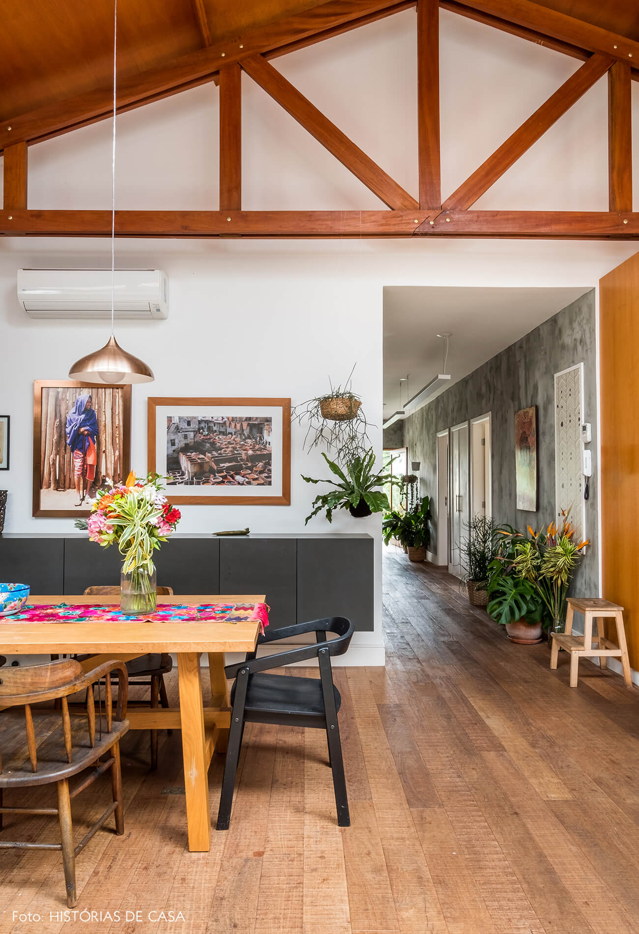 Sala de jantar com piso de madeira de demolição e vigas aparentes