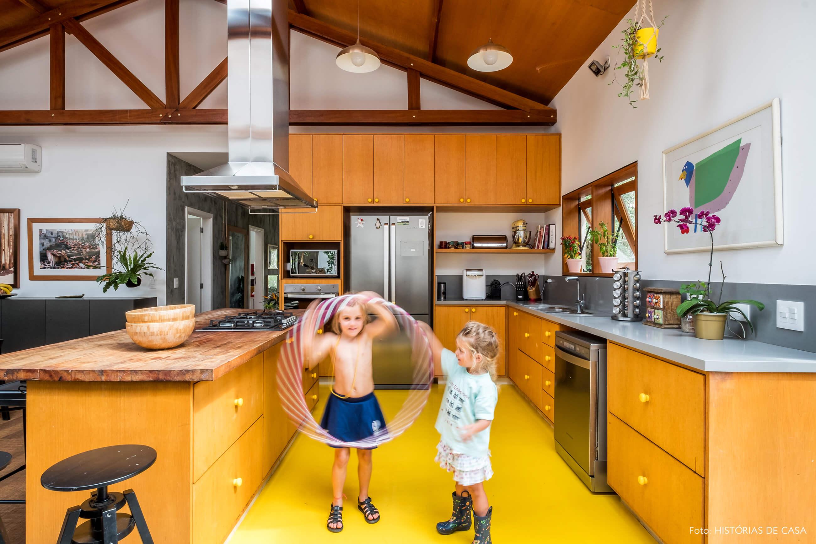Cozinha com piso amarelo e forro de madeira