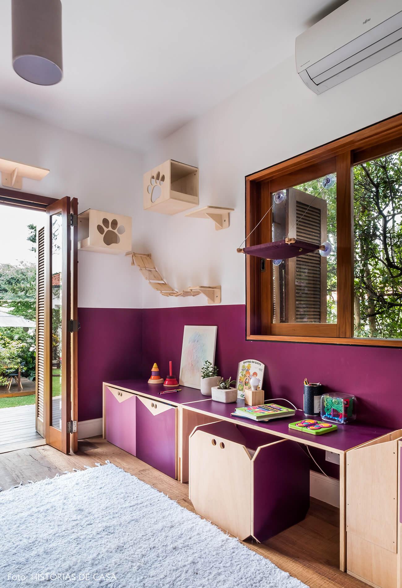 Casa com jardim e brinquedoteca colorida para as crianças. Paredes pintadas de roxo.