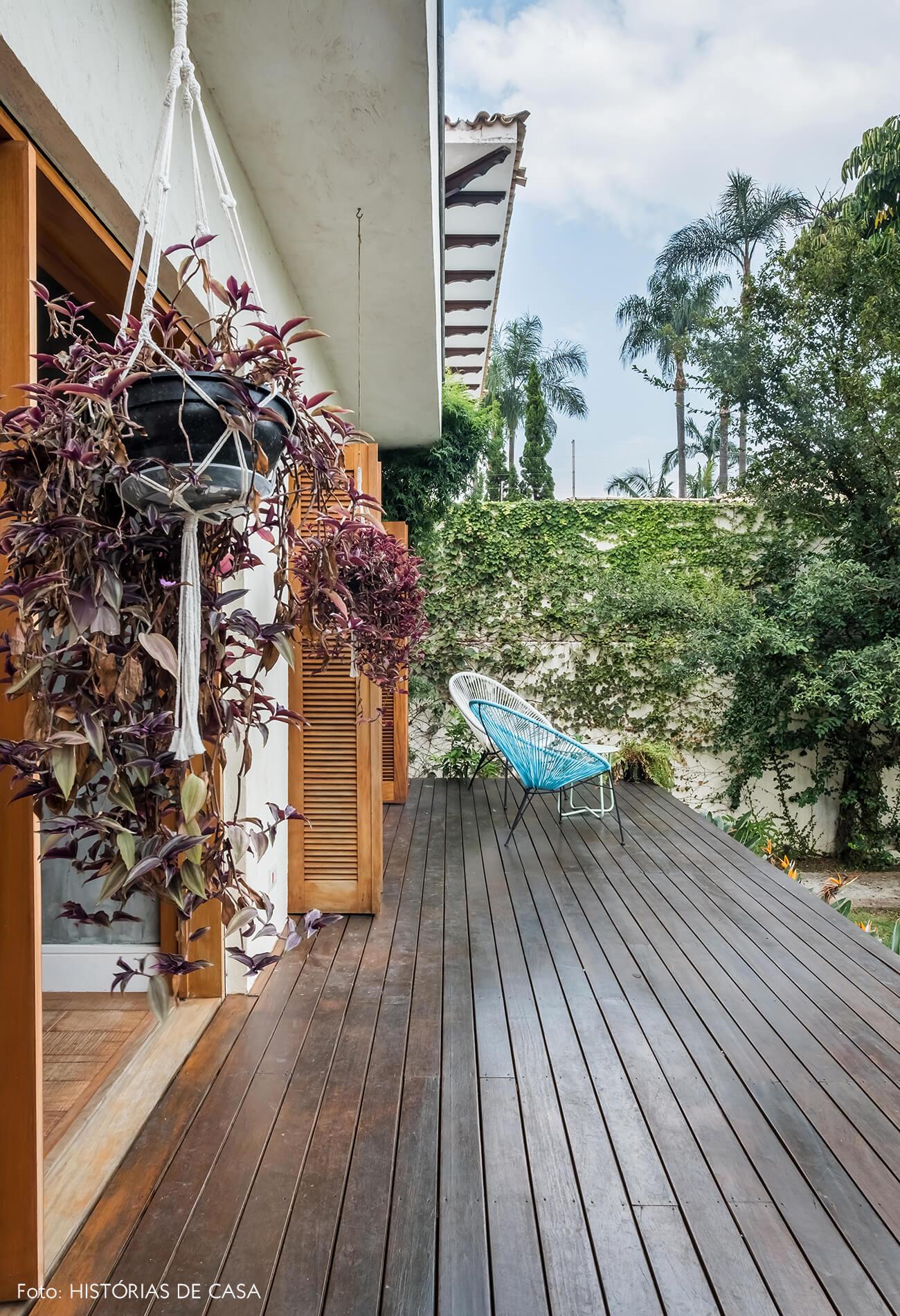 Casa com jardim nos fundos. Deck elevado e muitas plantas.