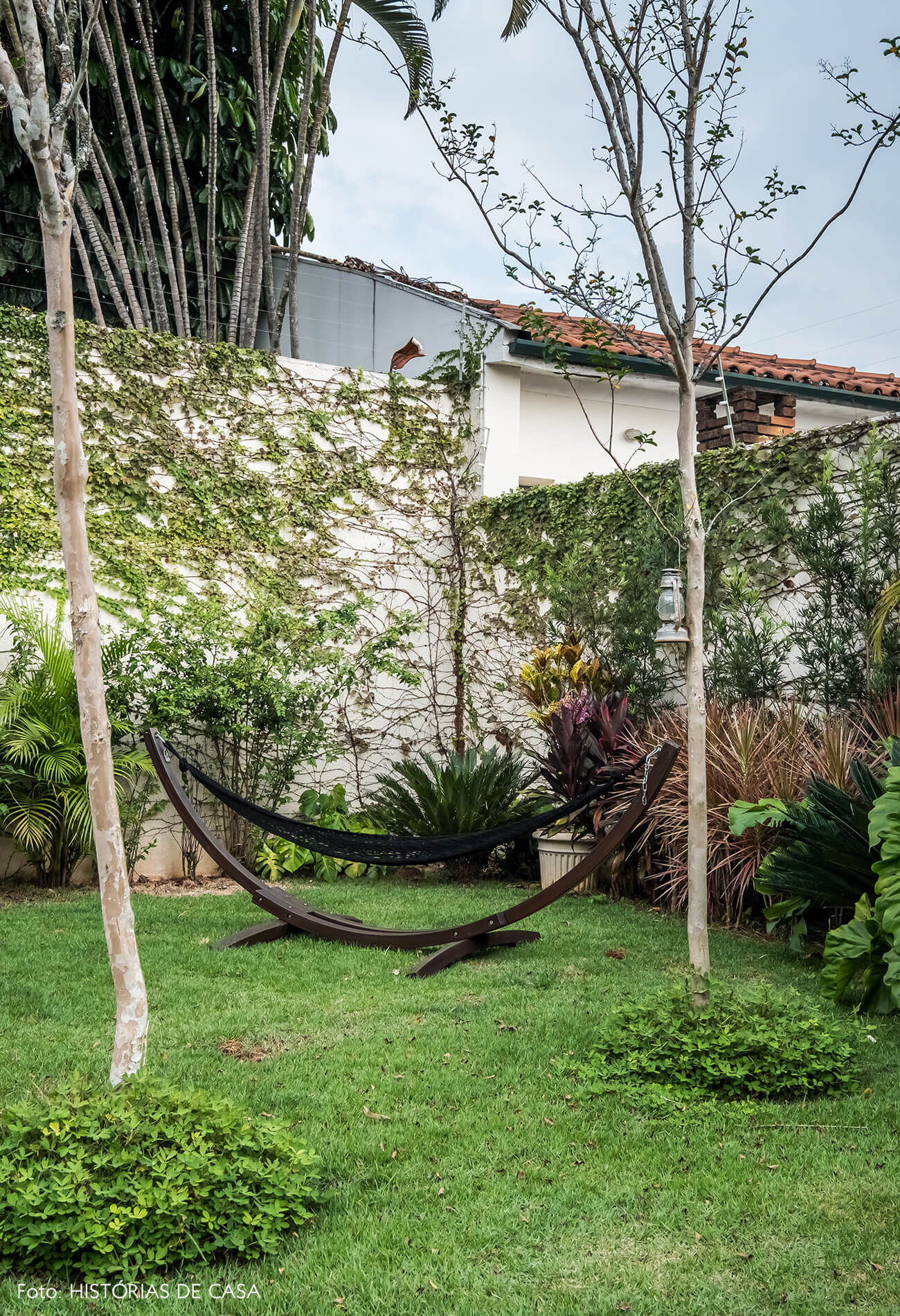Casa com jardim nos fundos. Gramado, deck e rede de balanço.