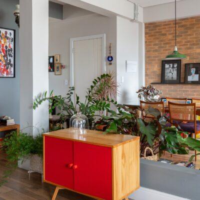 Apartamento pequeno com divisória de plantas e móvel colorido
