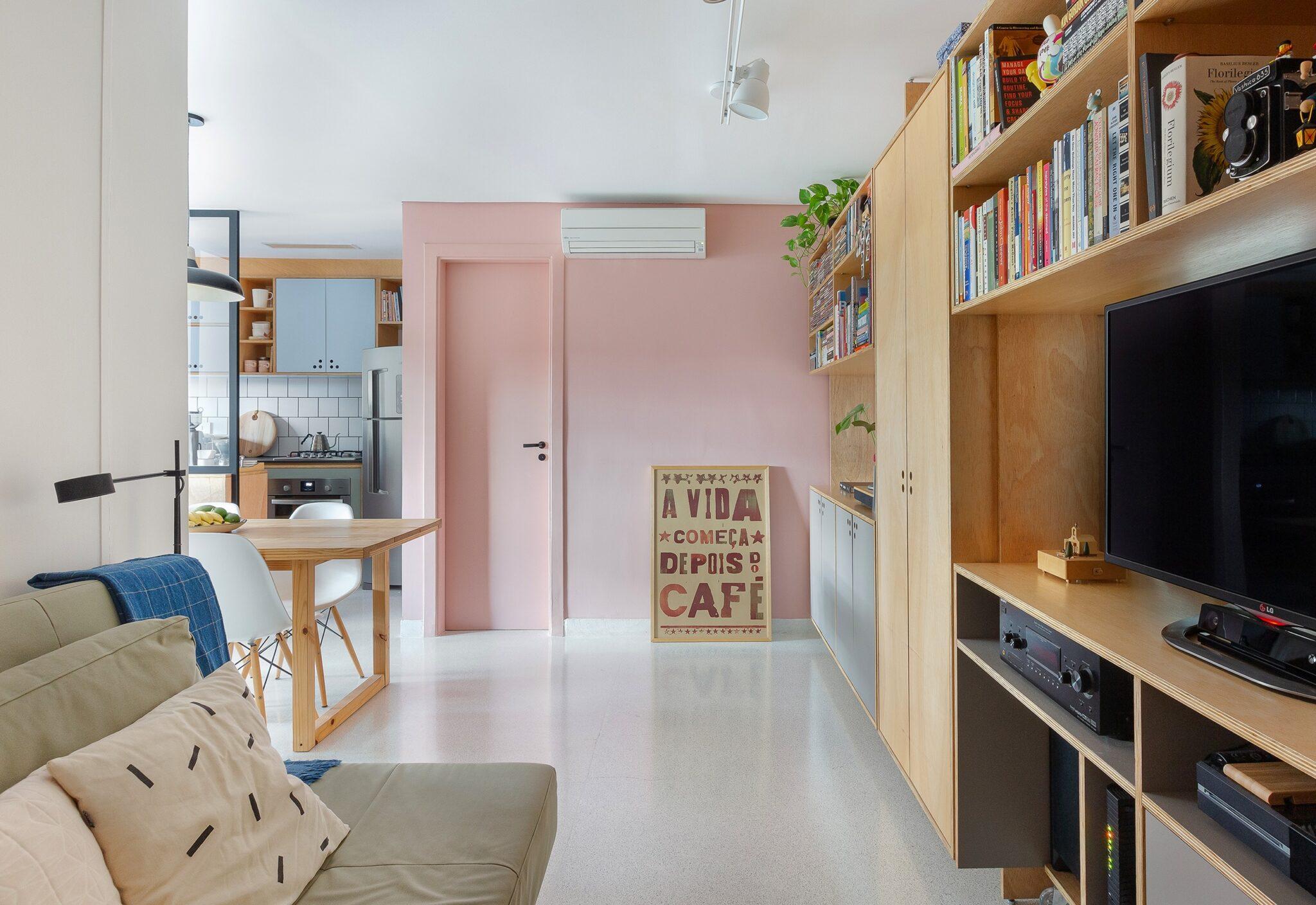 Apartamento pequeno com tons claros e parede rosa, ambientes integrados