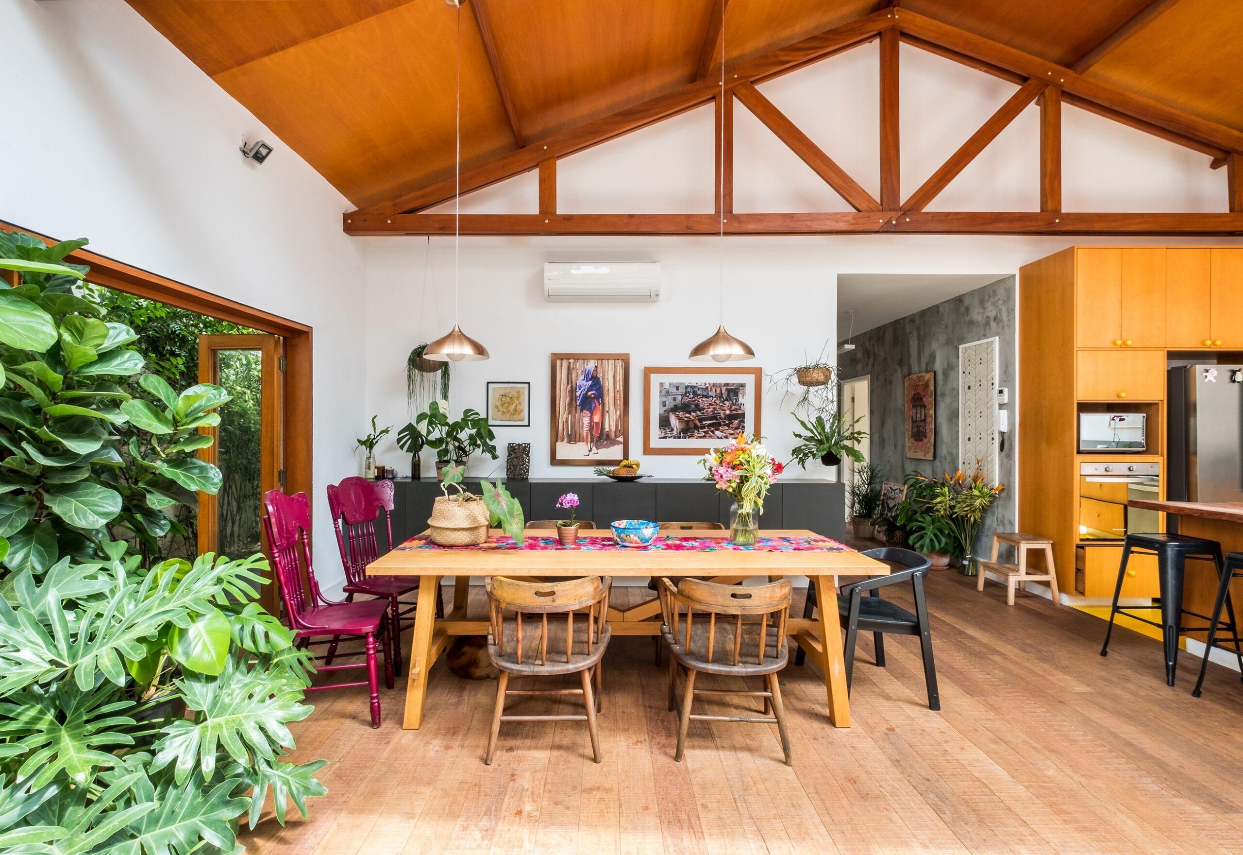 Casa térrea com forro de madeira, espaços abertos e muitas plantas