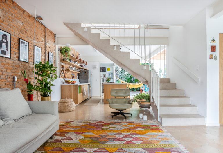 Sala integrada com escada no centro e tapete colorido
