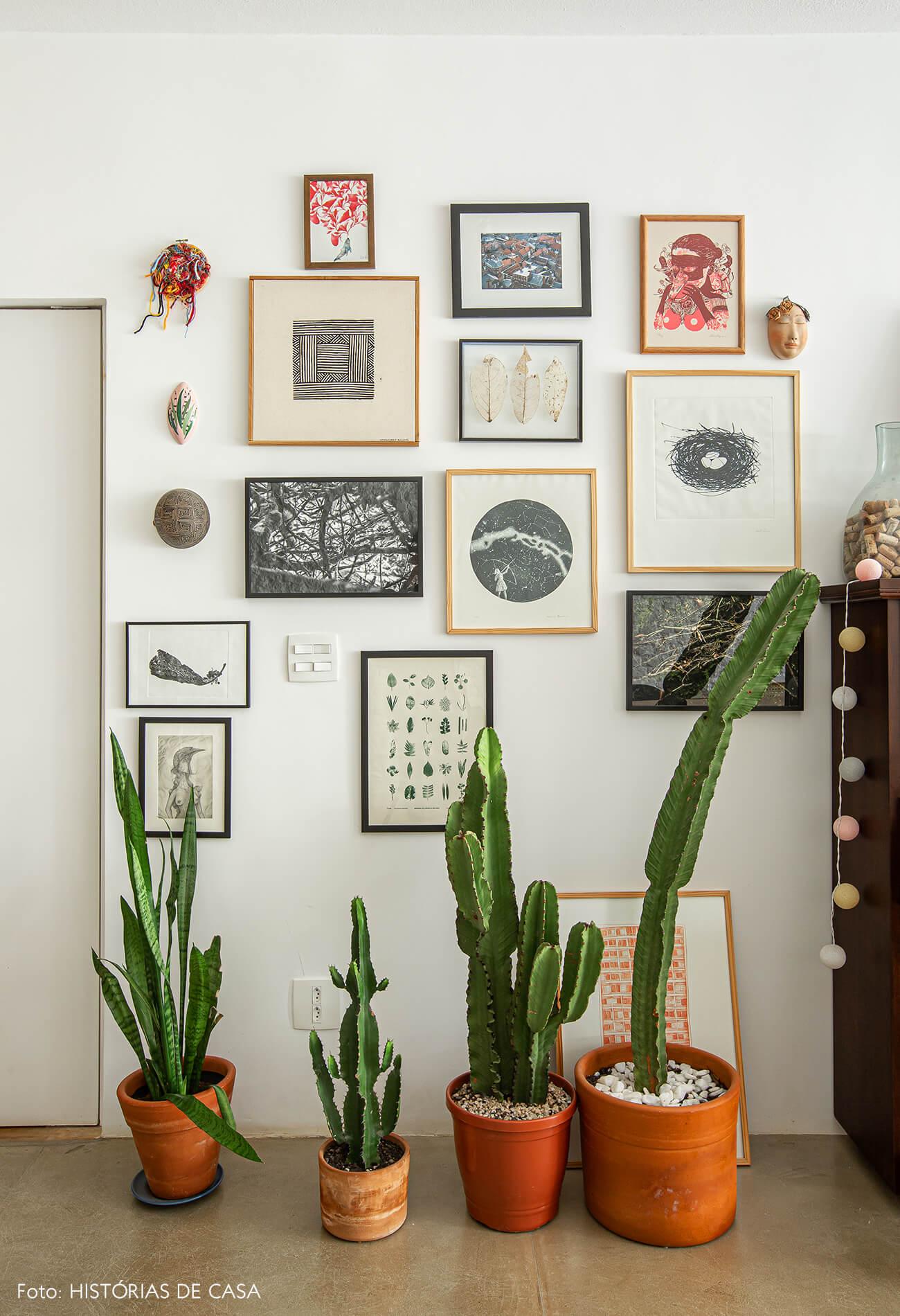 Apartamento térreo, parede de quadros e vasos de cactos