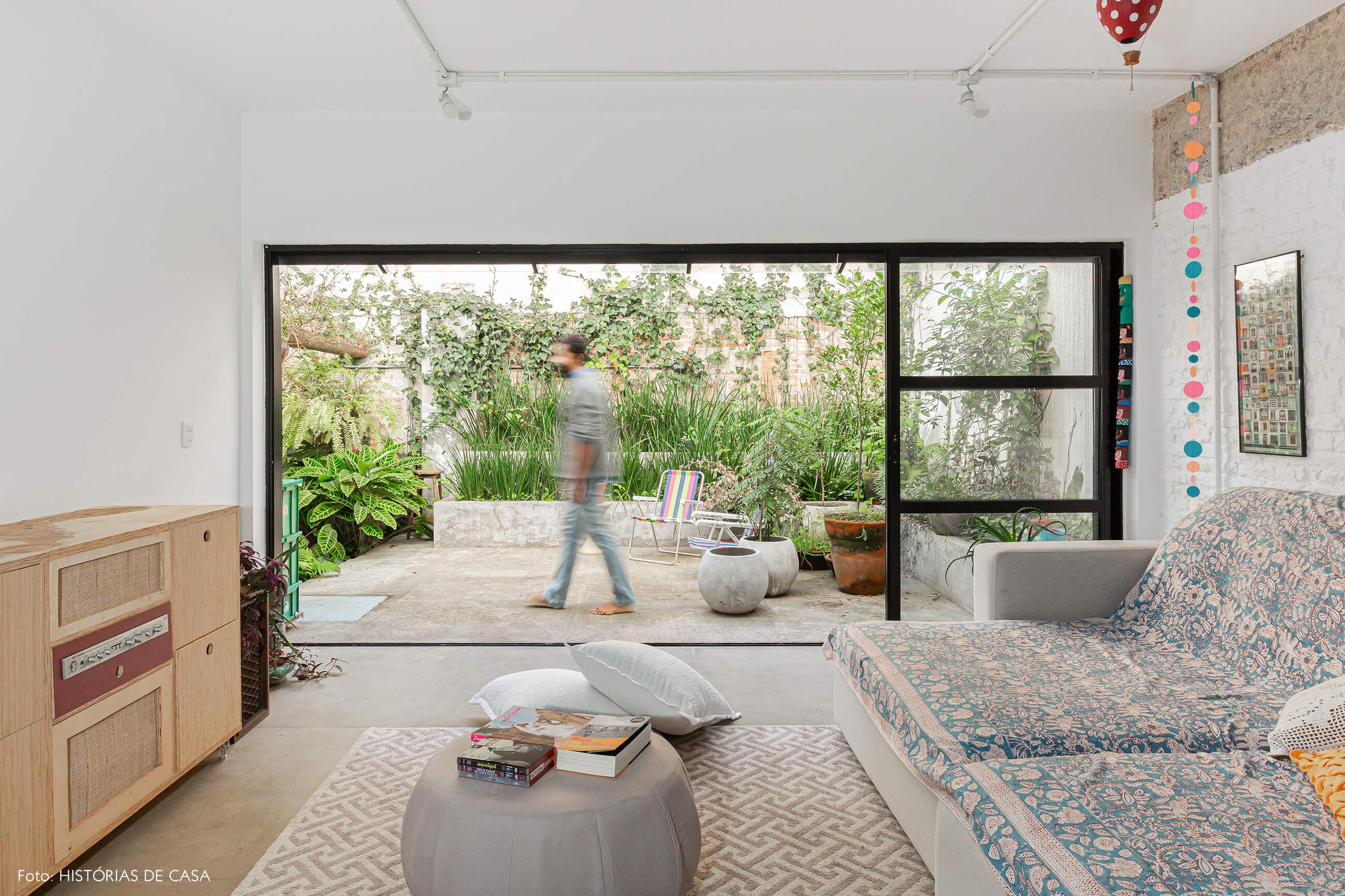 Apartamento térreo, sala integrada ao jardim e parede de tijolinhos brancos