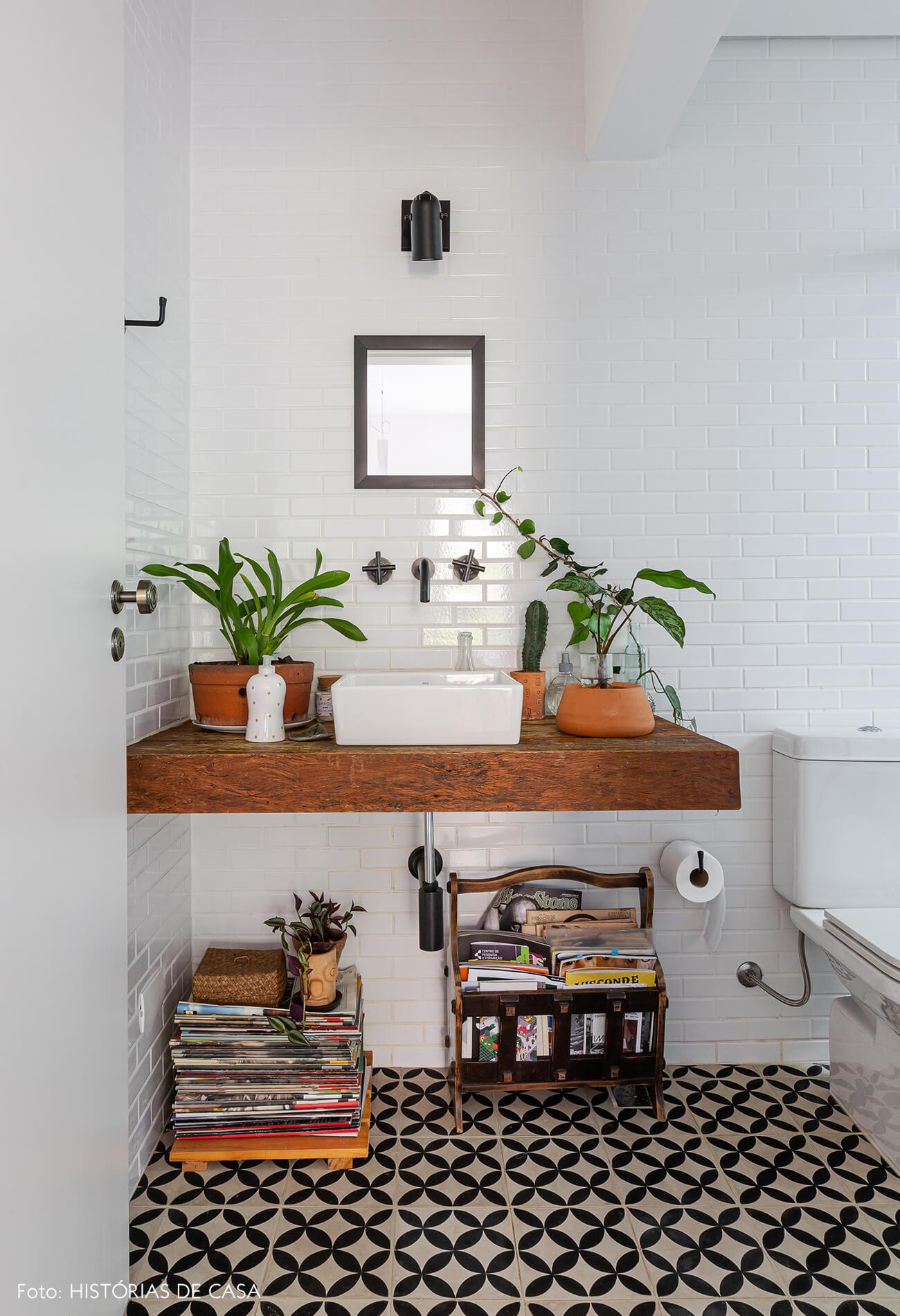 Banheiro com piso de ladrilhos e bancada de madeira