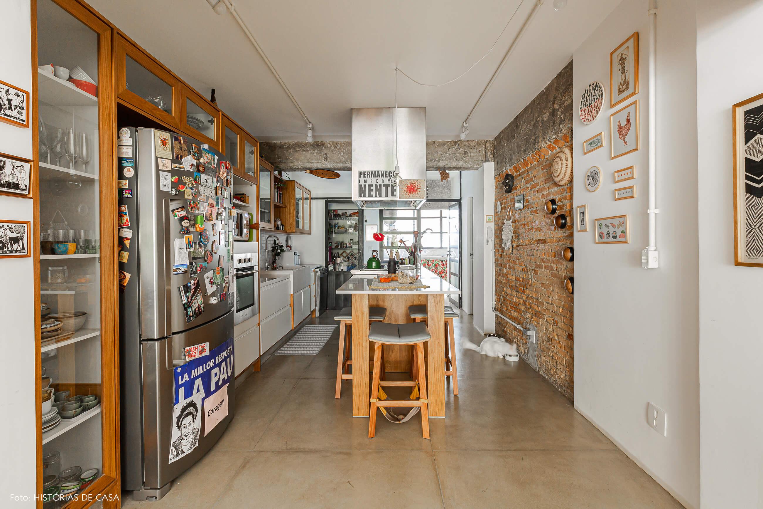 Apartamento térreo, cozinha com paredes de tijolinho e bancada central