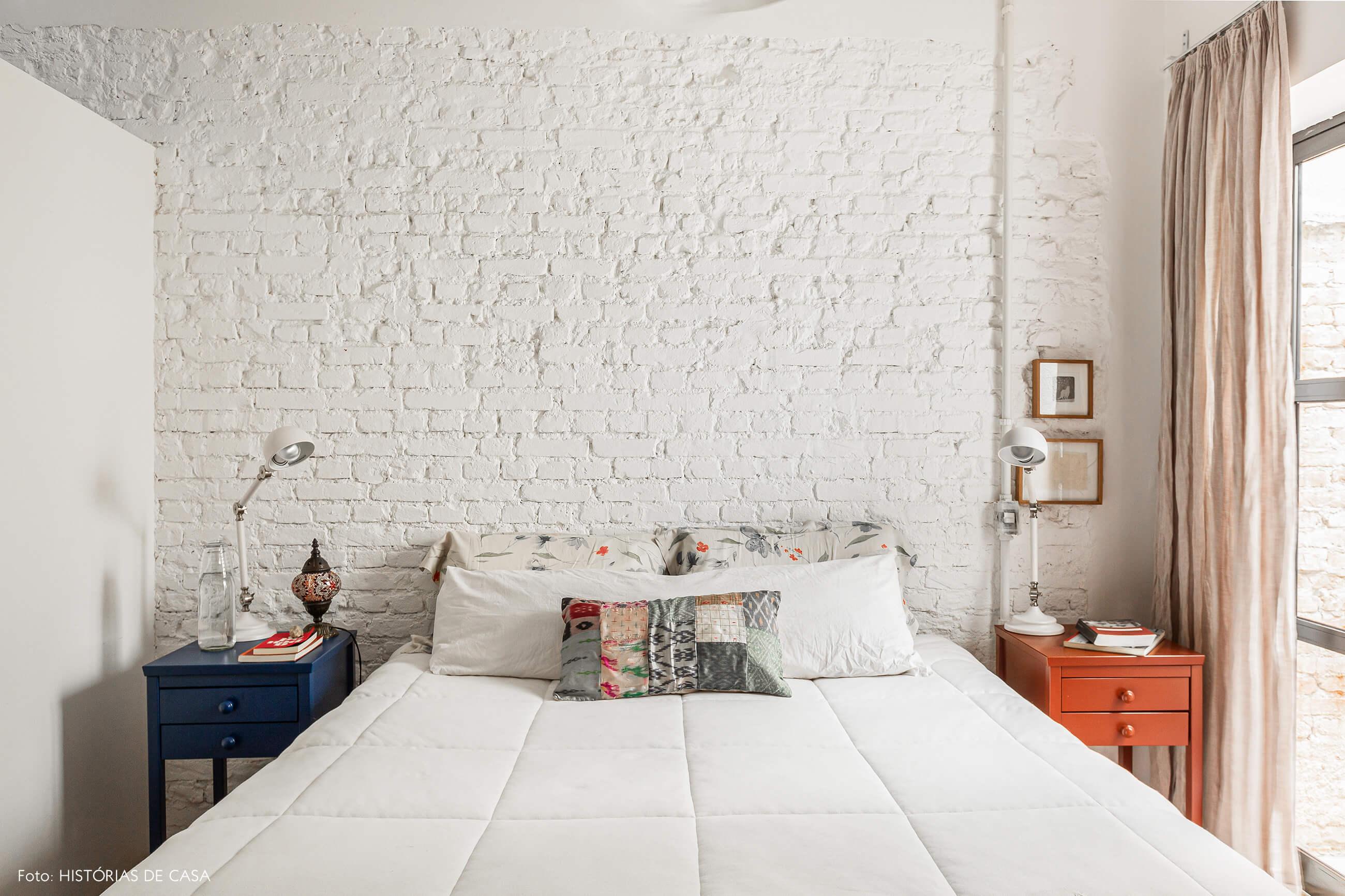 Apartamento térreo, quarto com parede de tijolinho branco e vista para o jardim