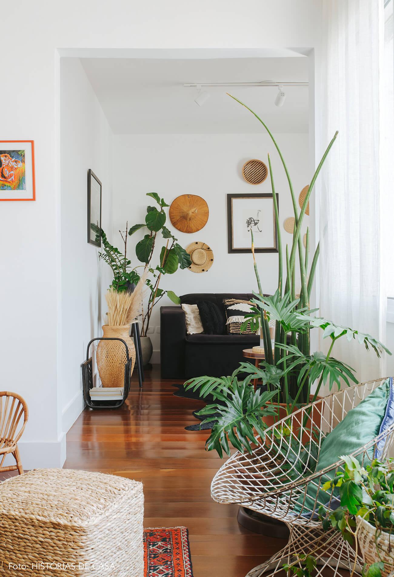 Apartamento da chef Renata Vanzetto, sala com sofá preto e chapéus na parede