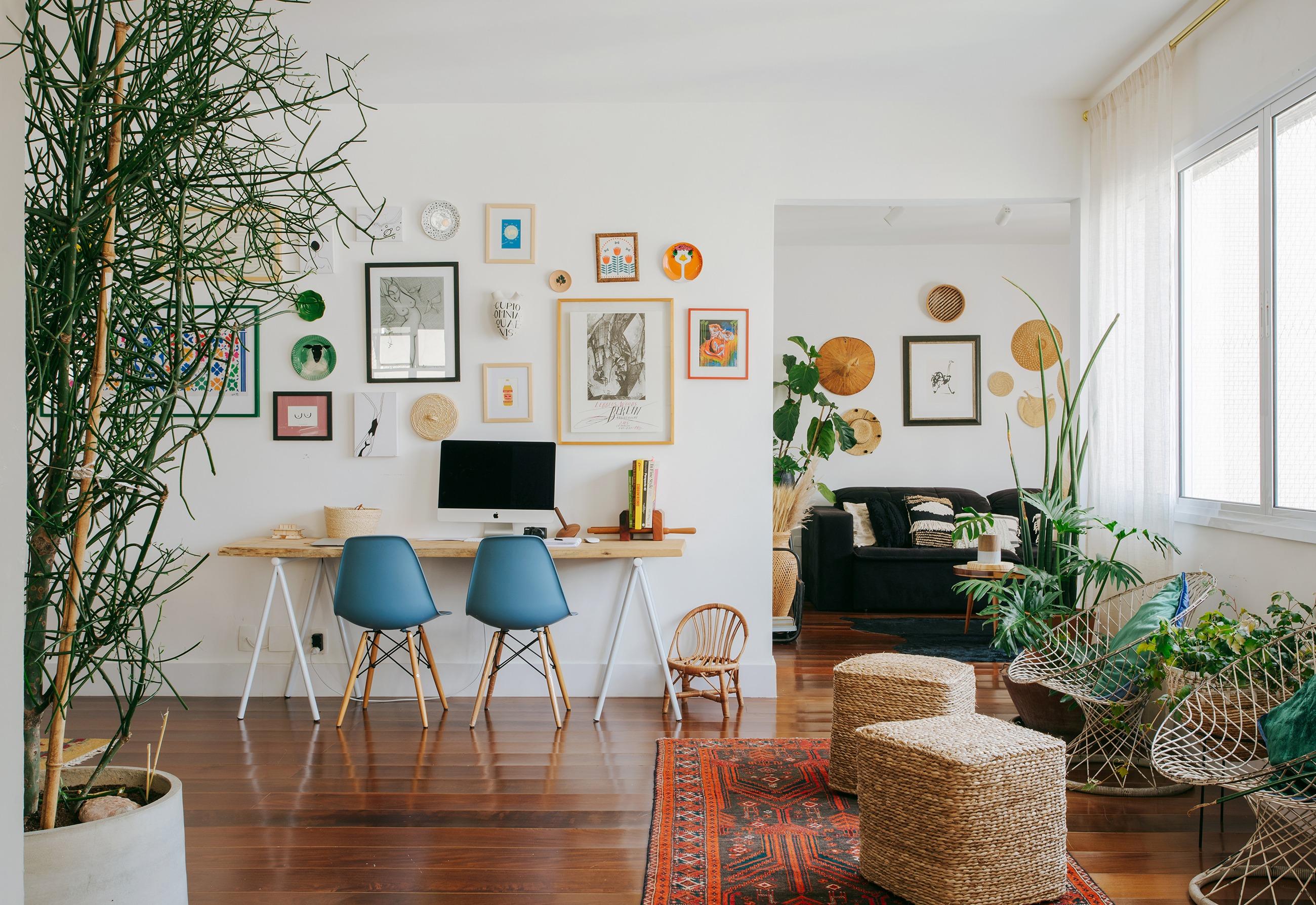 Apartamento com home office na sala, parede de quadros