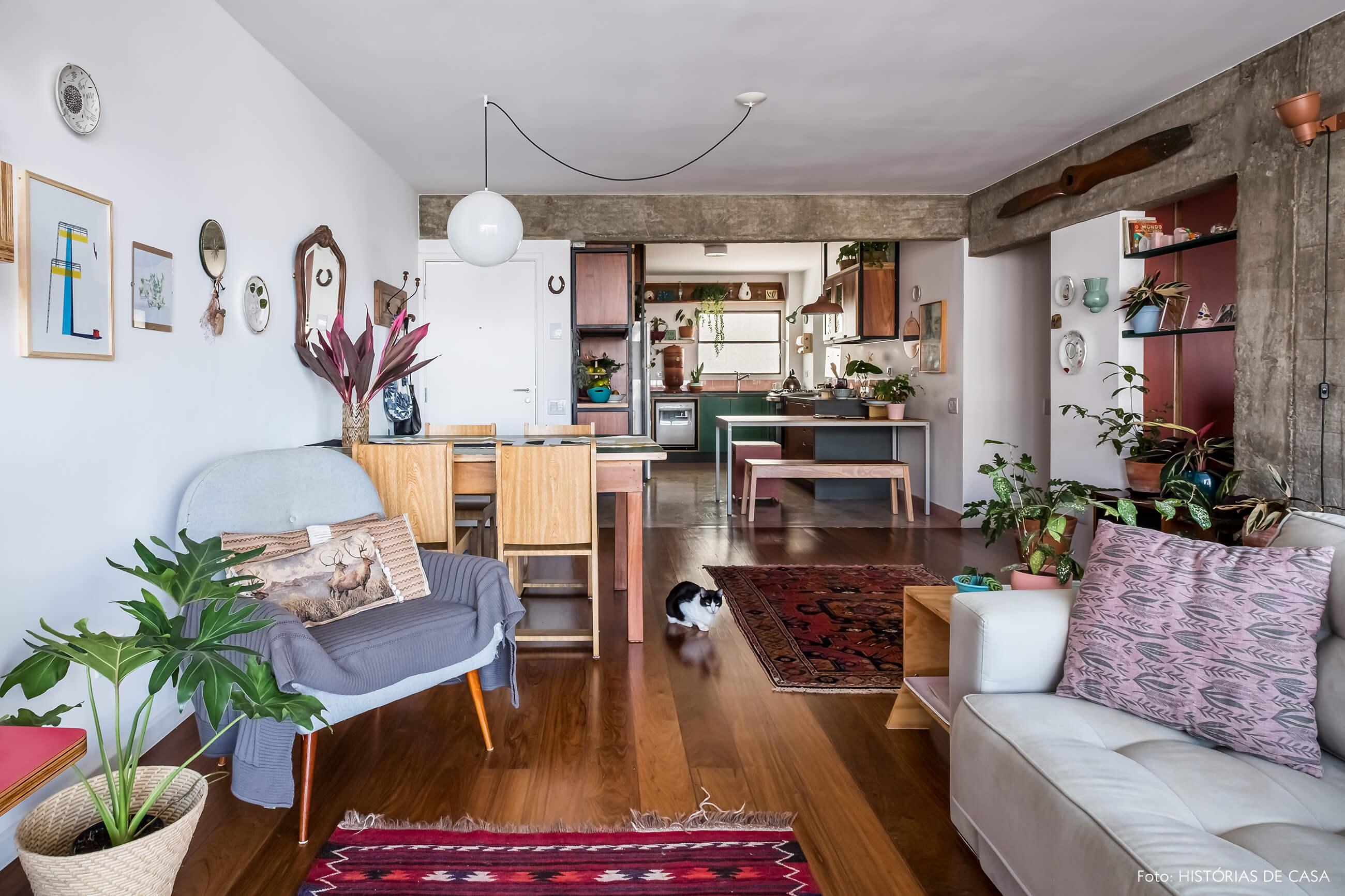 Apartamento com sala integrada e piso de madeira, pilares de concreto e plantas