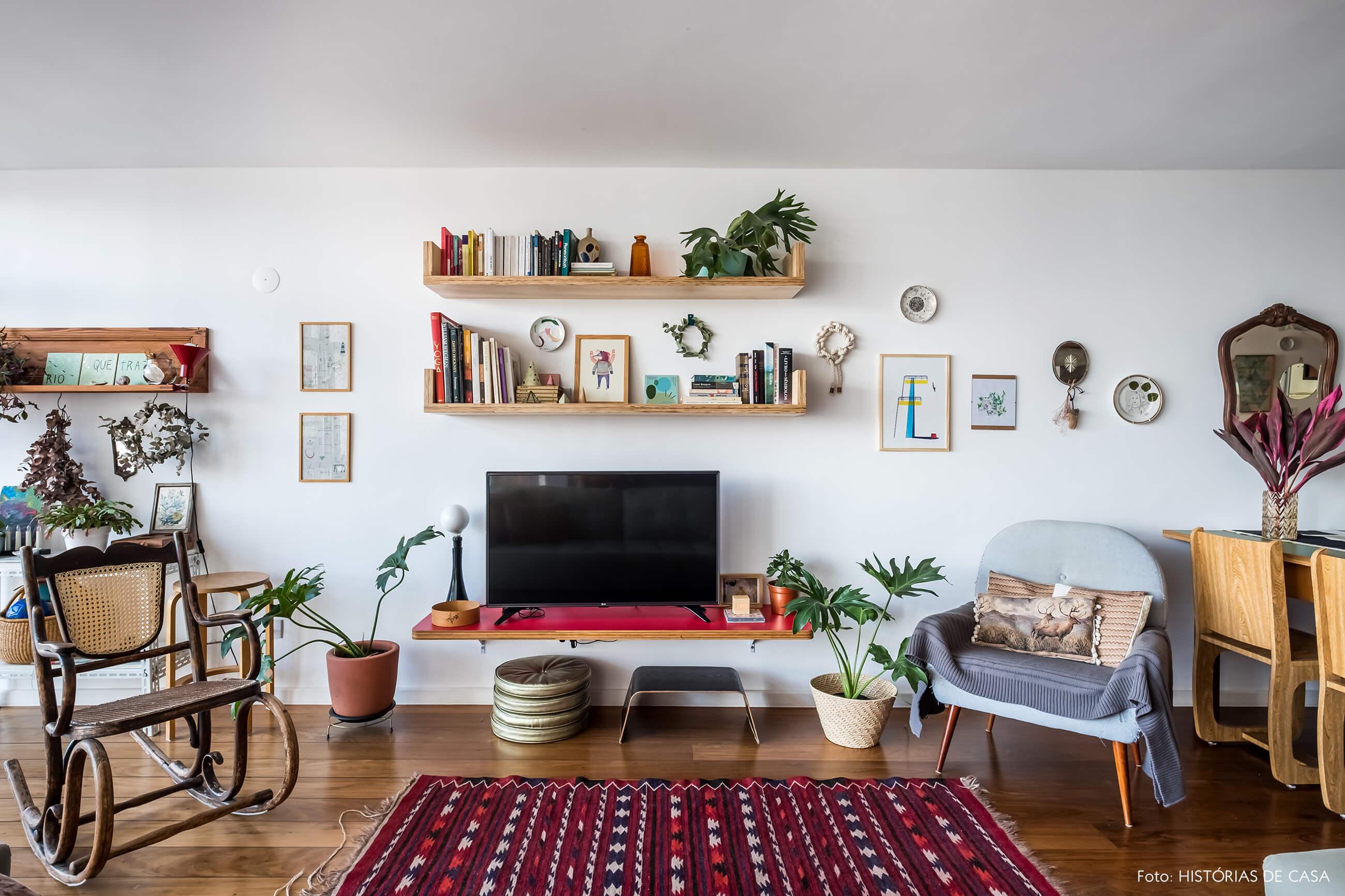 Sala com prateleiras na parede da TV