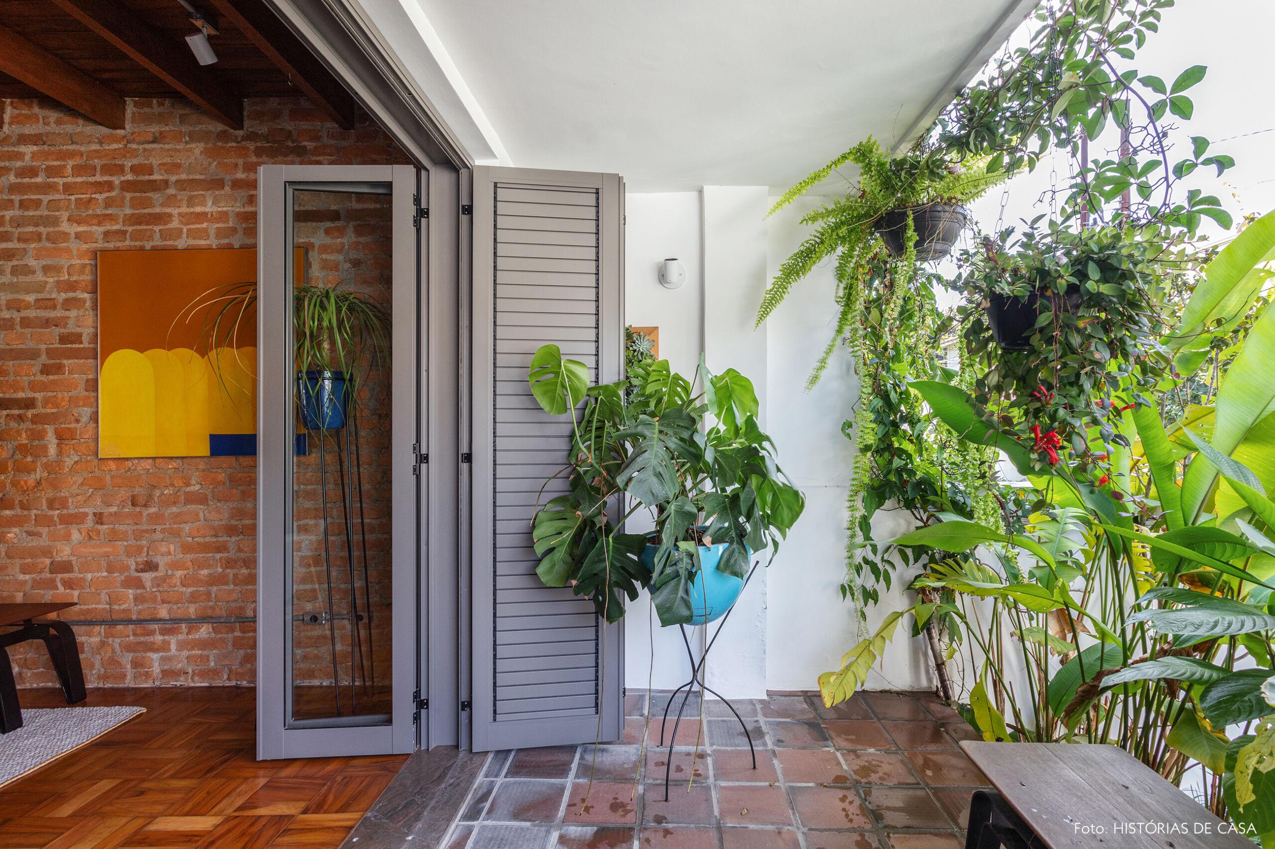 Sala com parede de tijolinho e varanda com plantas