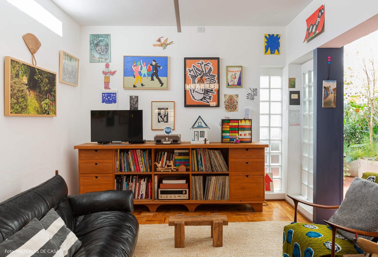 Apartamento reformado, sala com parede de quadros e detalhes coloridos