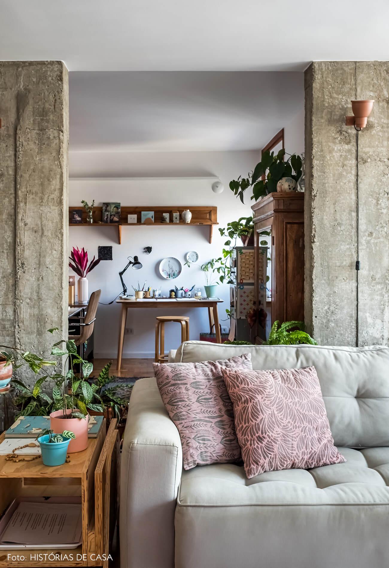 Sala reformada, estrutura de concreto à mostra e sofá cinza