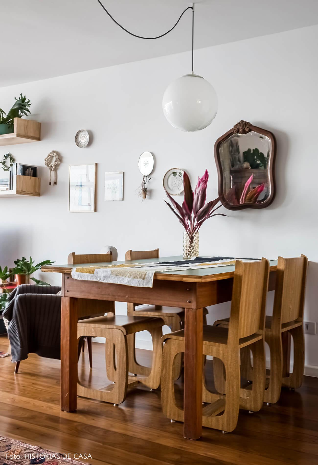 Sala de jantar com espelho vintage e luminária de globo branco