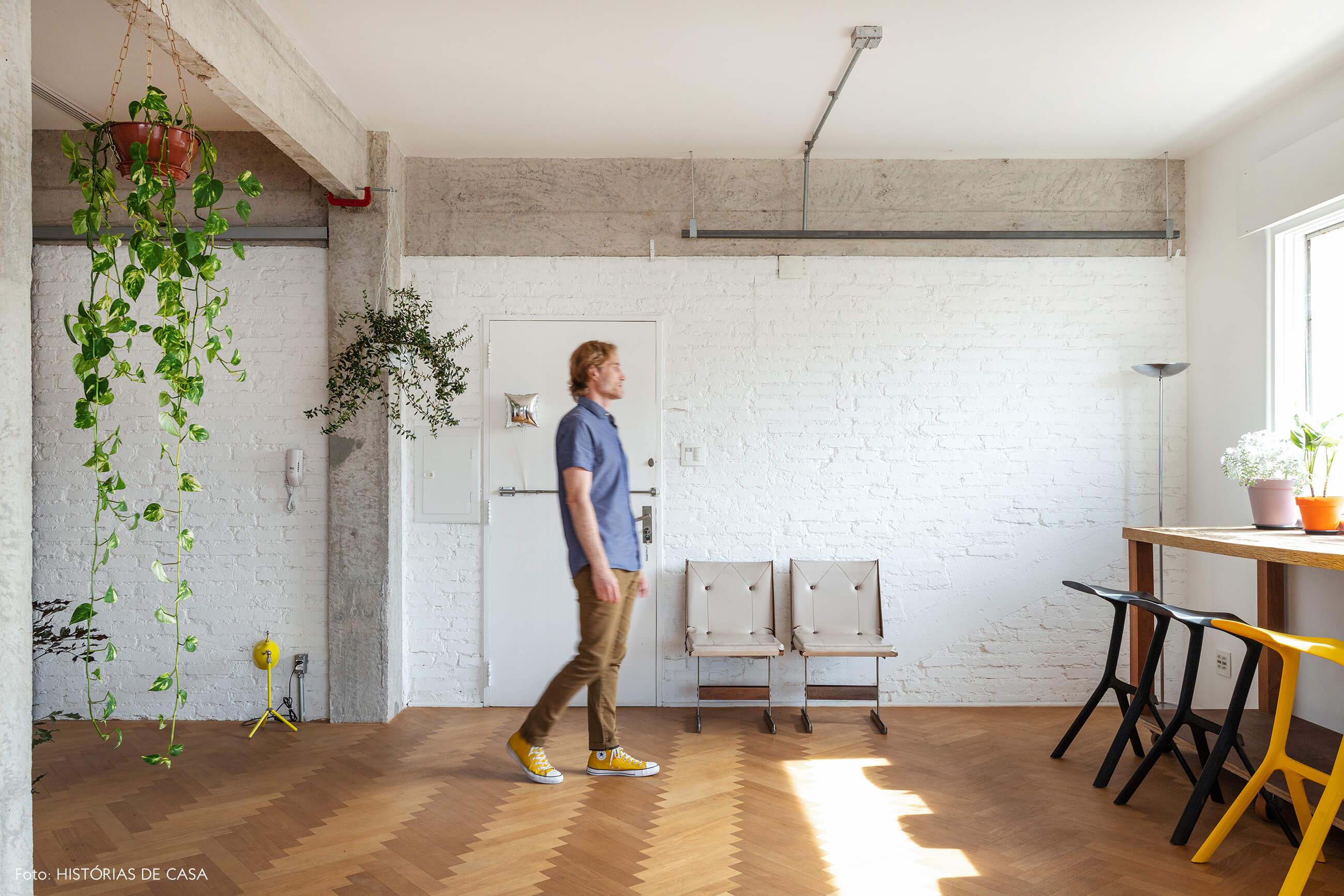 Apartamento integrado com parede de tijolinho branco e piso de madeira
