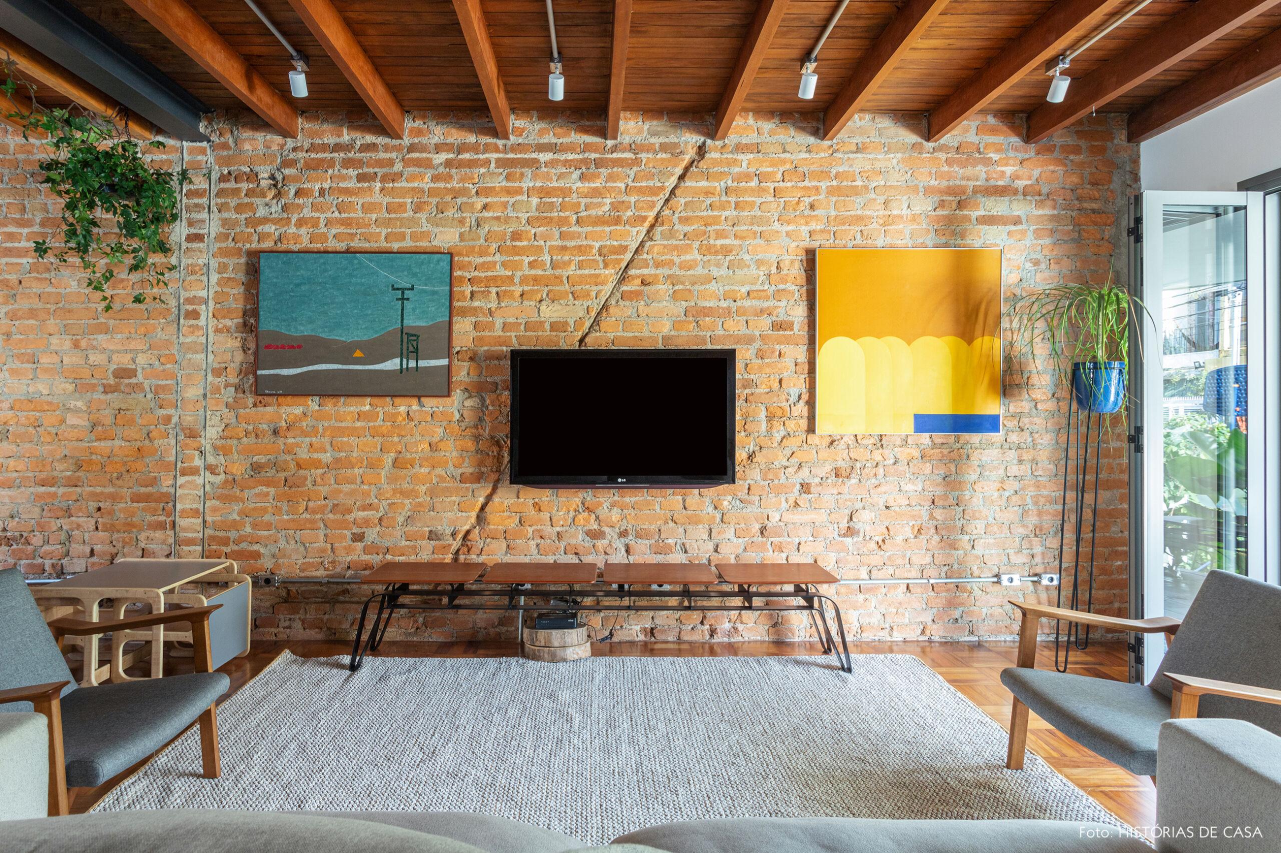 Casa antiga com parede de tijolinho na sala e forro de madeira