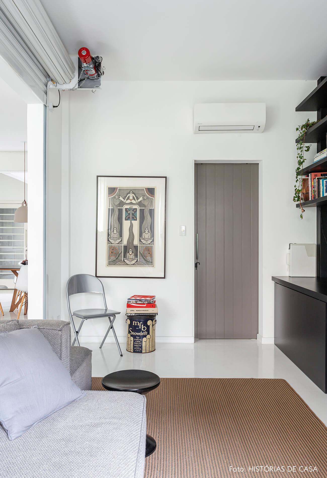 Apartamento escandinavo, sala com estante preta e porta cinza