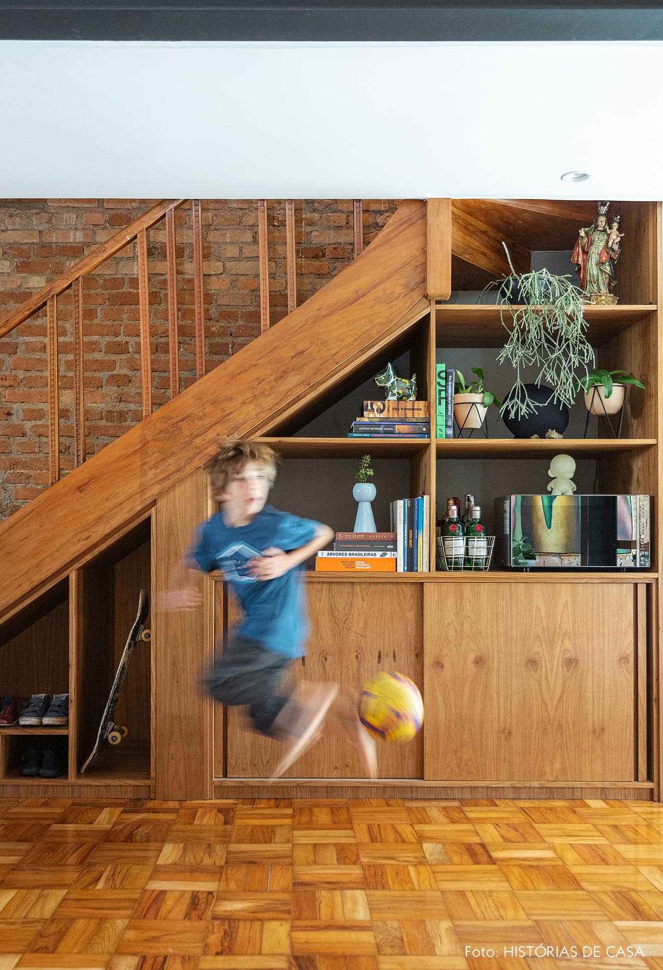 Escada de madeira com nicho para sapatos e armários sob o vão