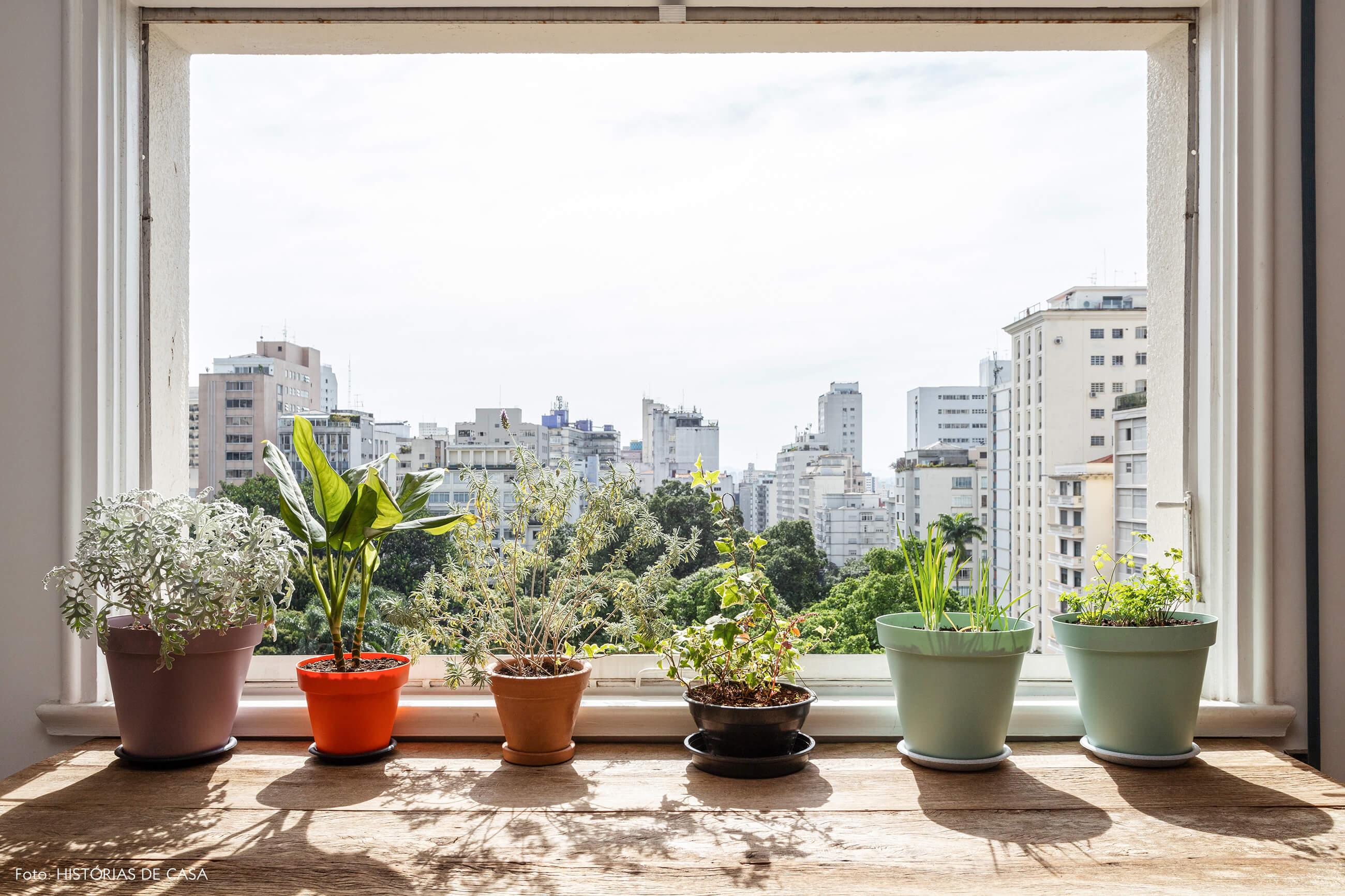 Apartamento integrado com parede de tijolinho branco e hora na janela