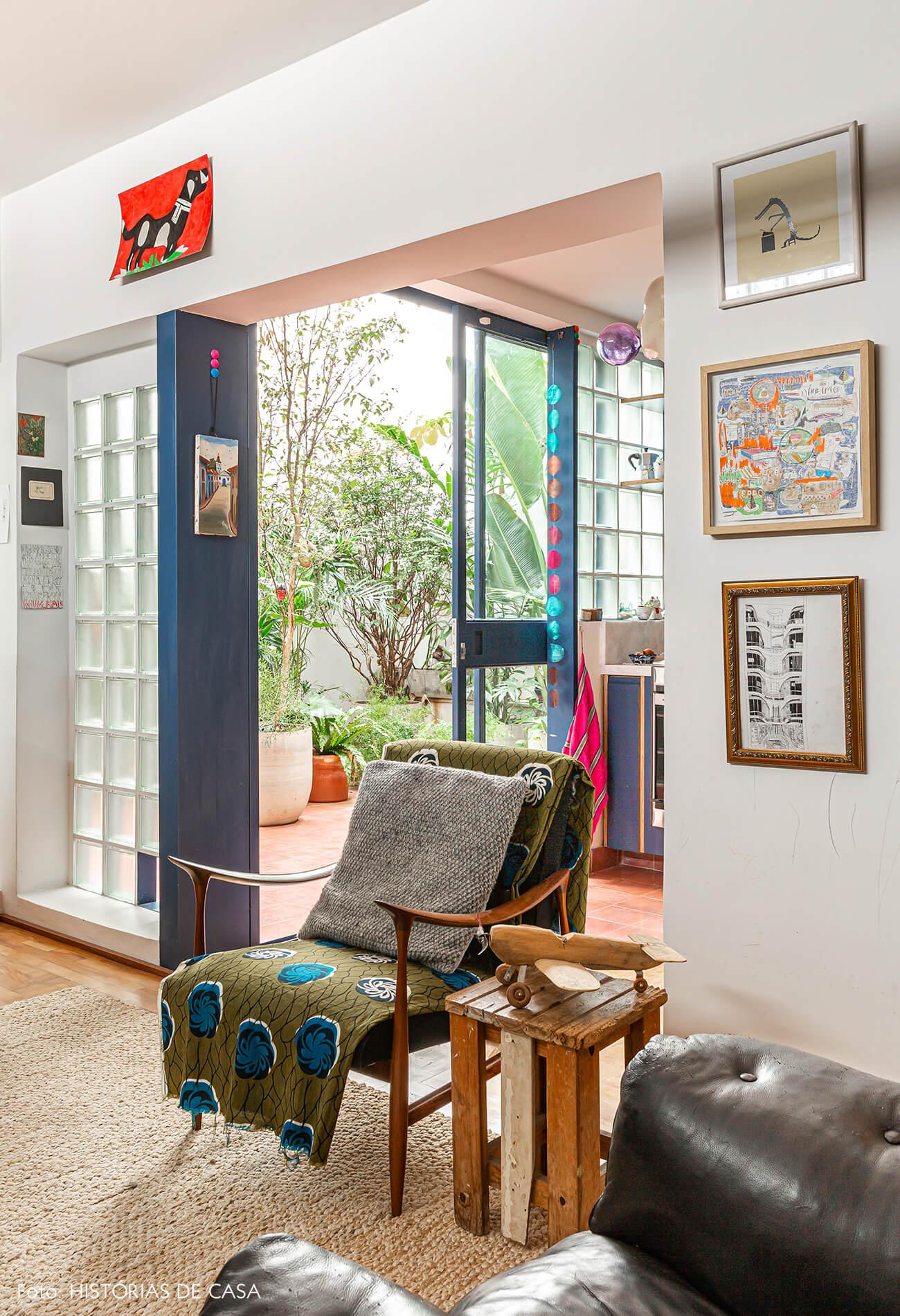 Apartamento reformado, sala com sofá de couro preto e poltrona vintage