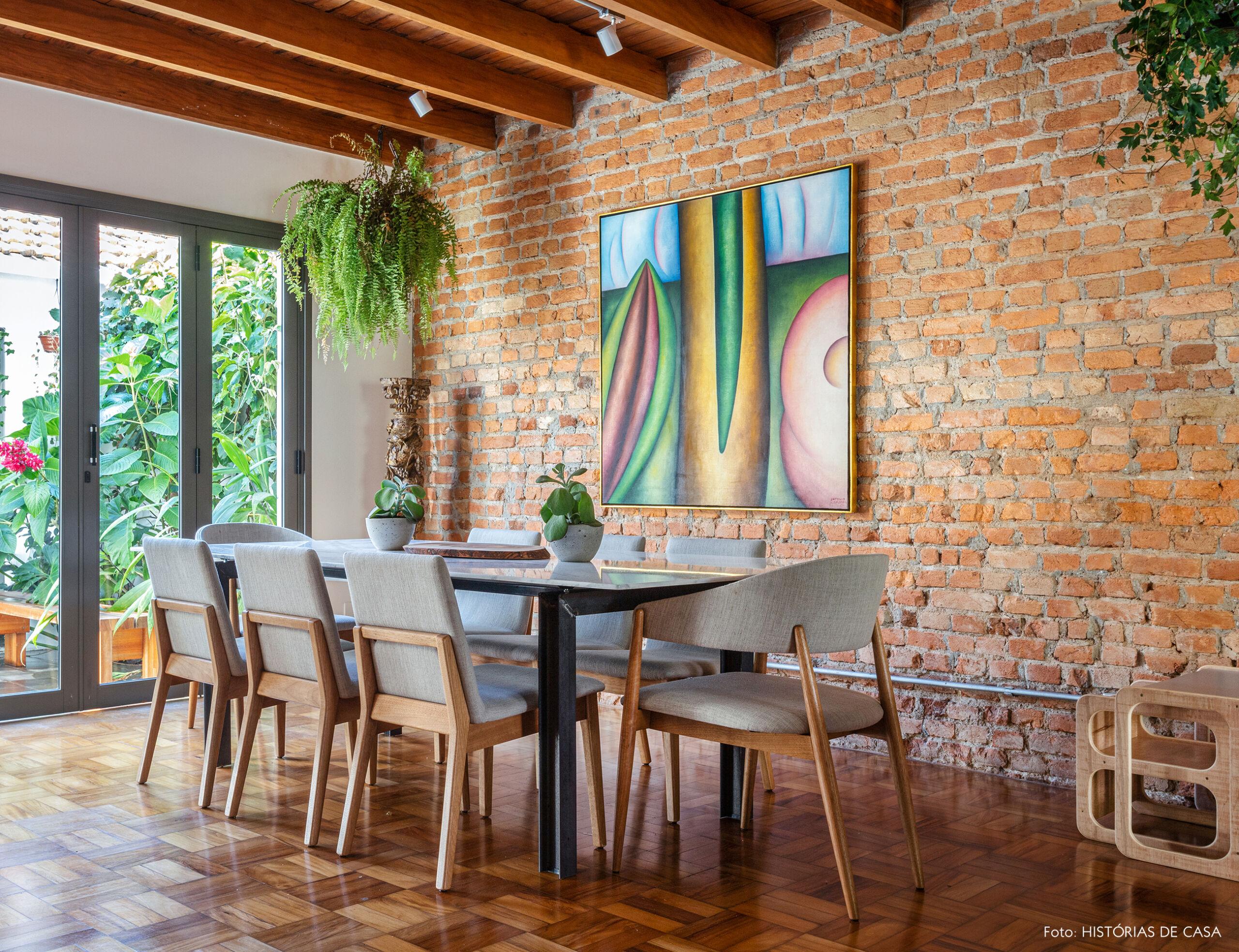 Sala de jantar com parede de tijolinho e forro de madeira