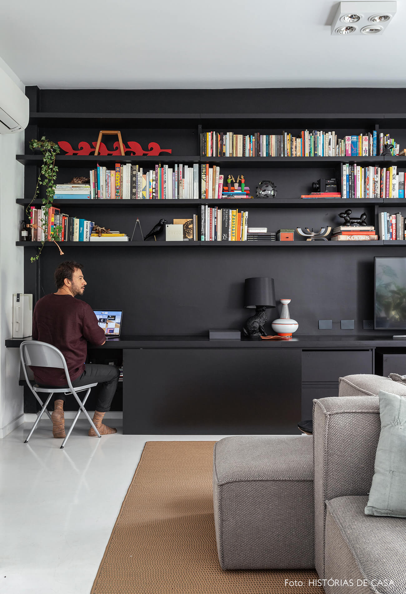 Apartamento escandinavo, sala com estante preta e home office