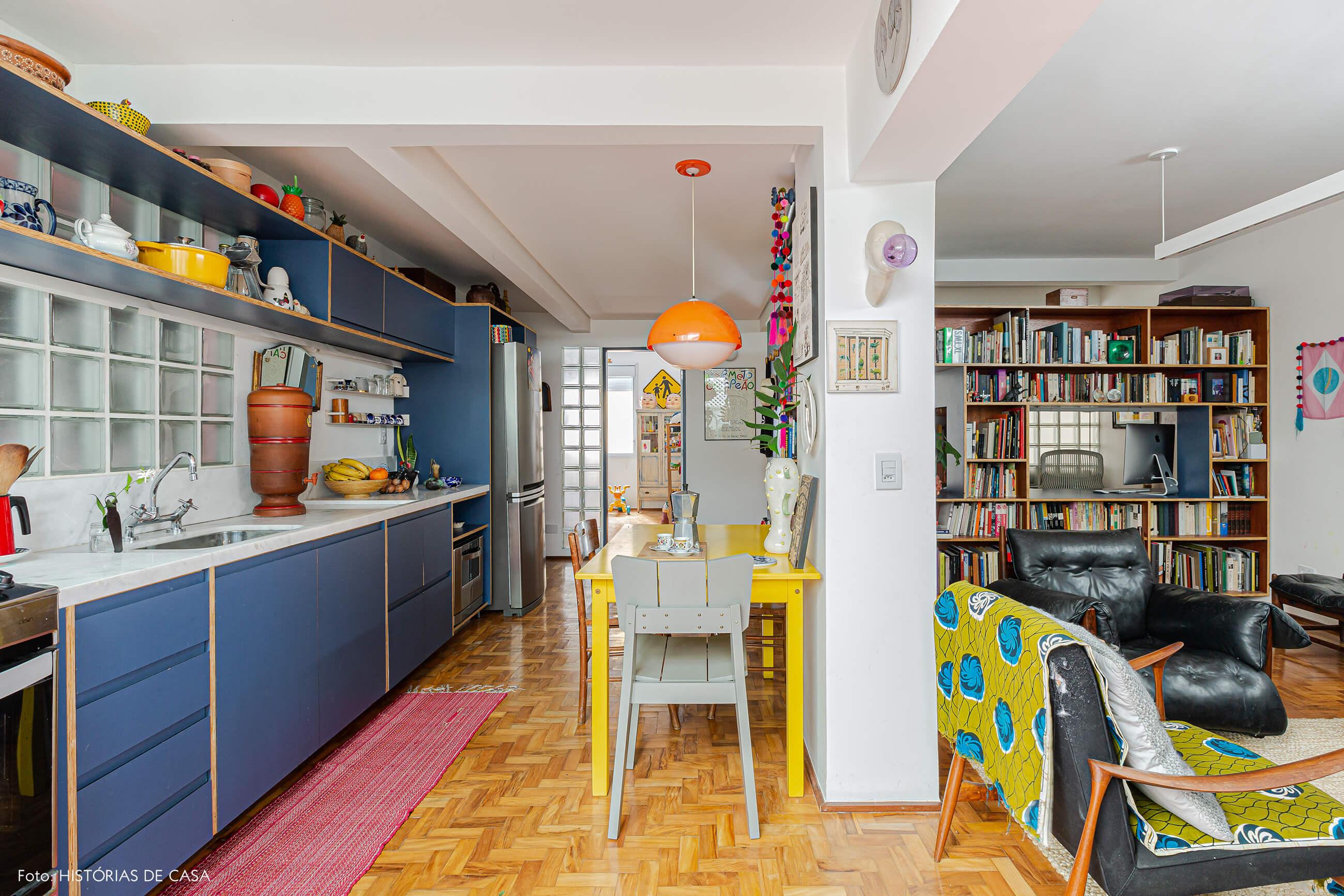Apartamento reformado, cozinha colorida integrada com mesa amarela