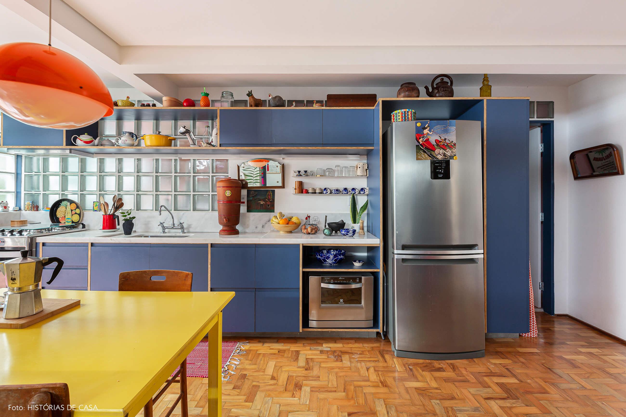 Apartamento reformado, cozinha com armários azuis e mesa amarela