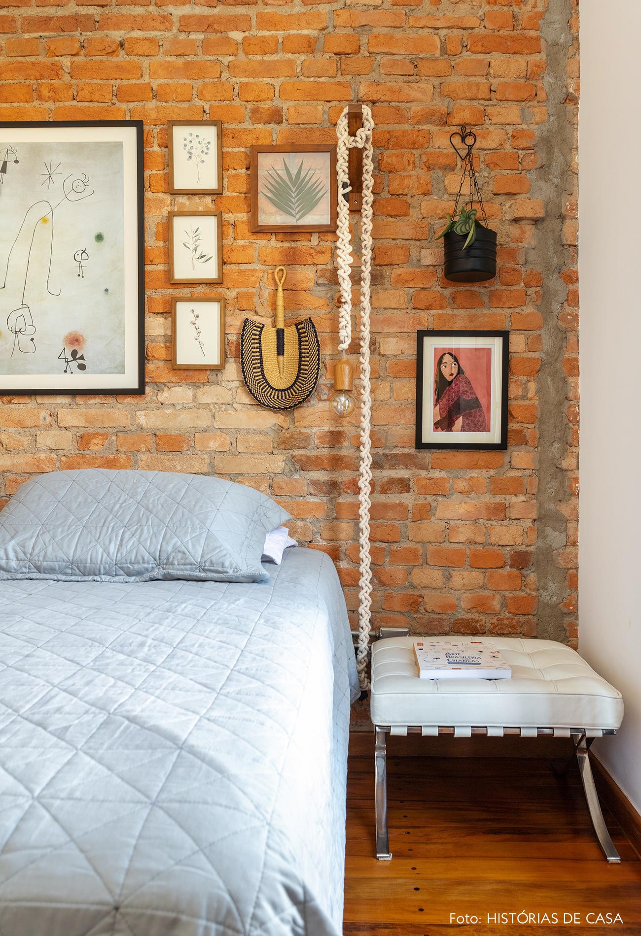 Quarto com parede de tijolinho e muitos quadros atrás da cama