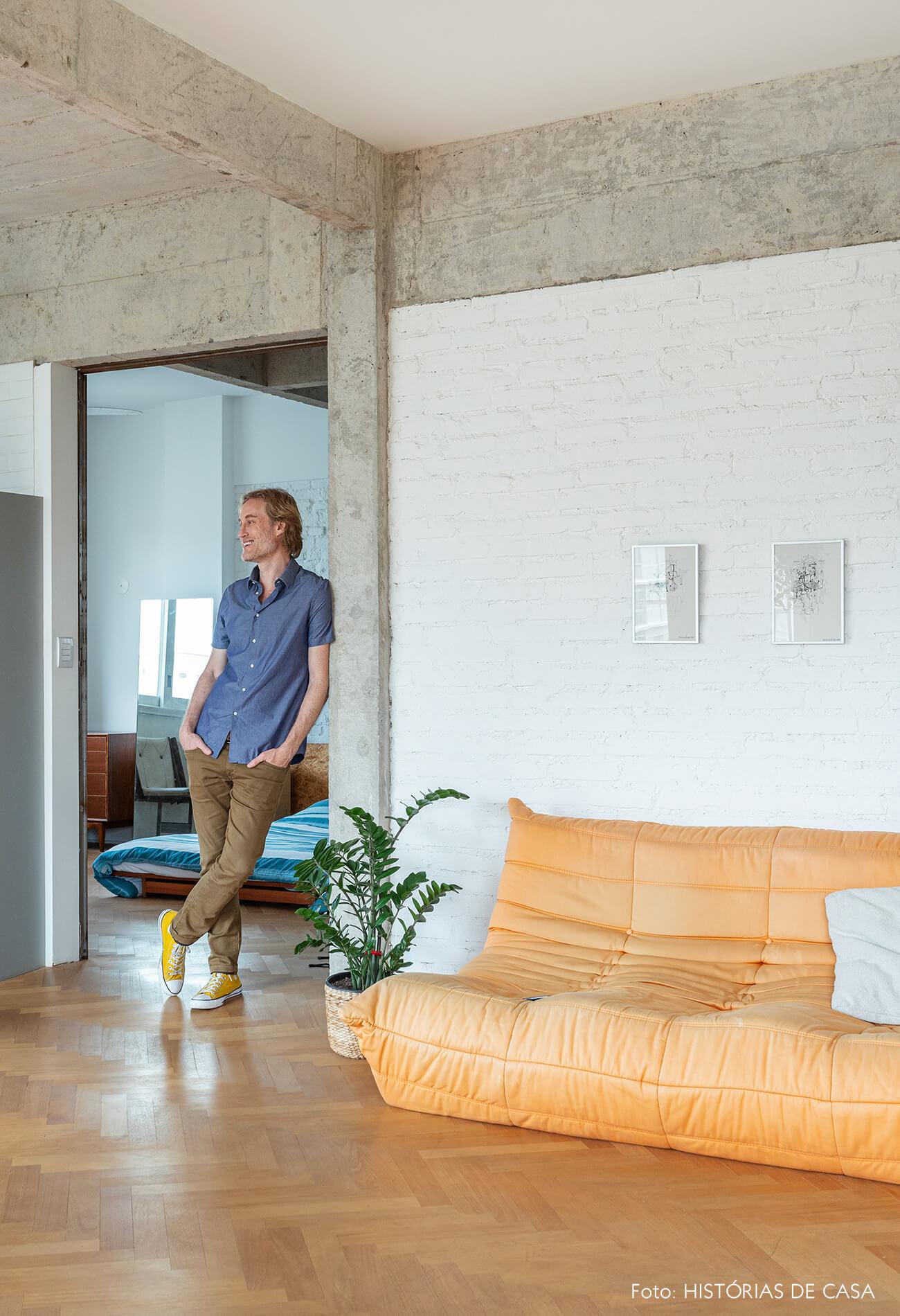 Apartamento integrado com parede de tijolinho branco e sofá laranja