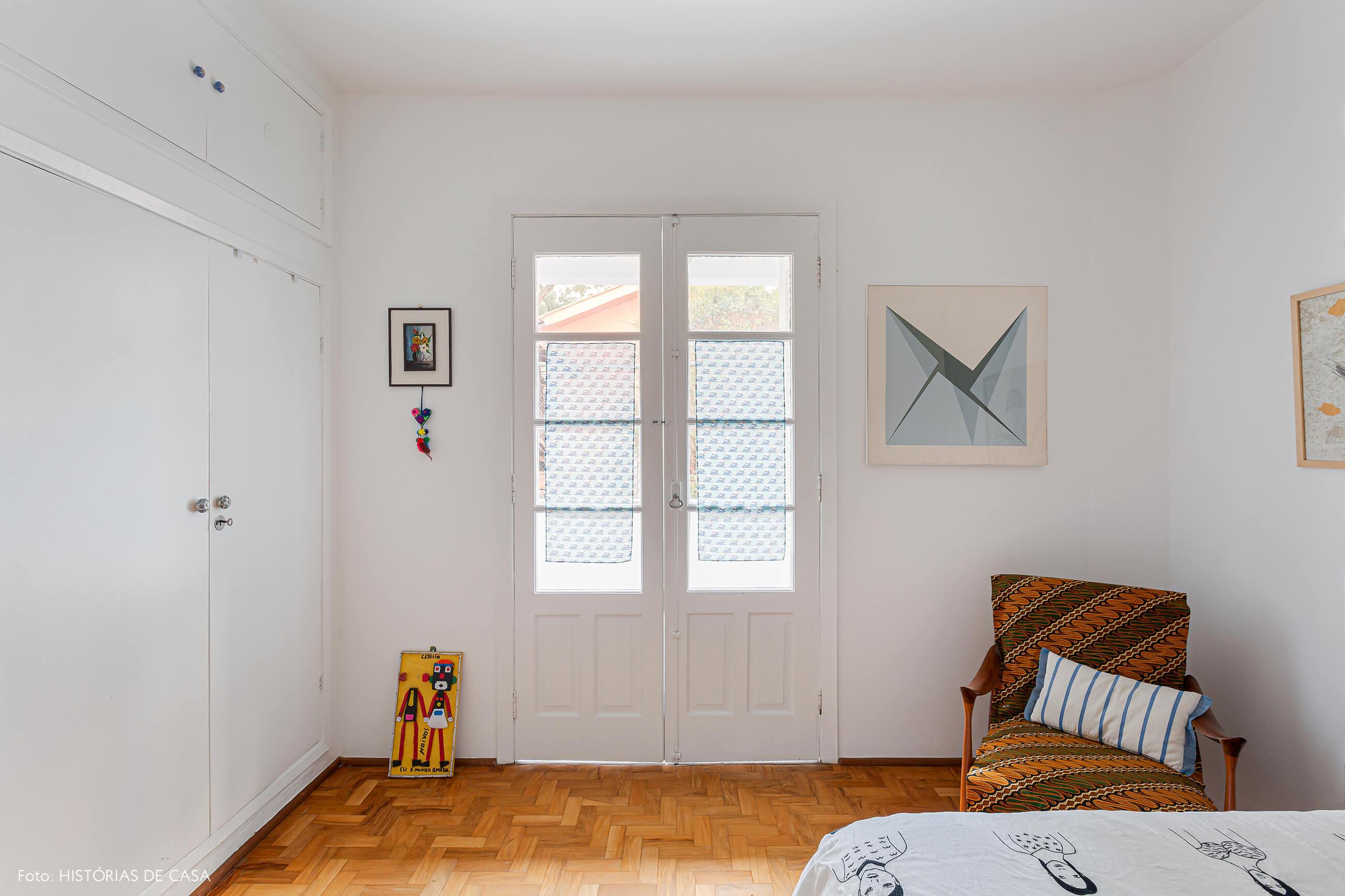 Quarto branco, parede de tijolos de vidro e portas de madeira