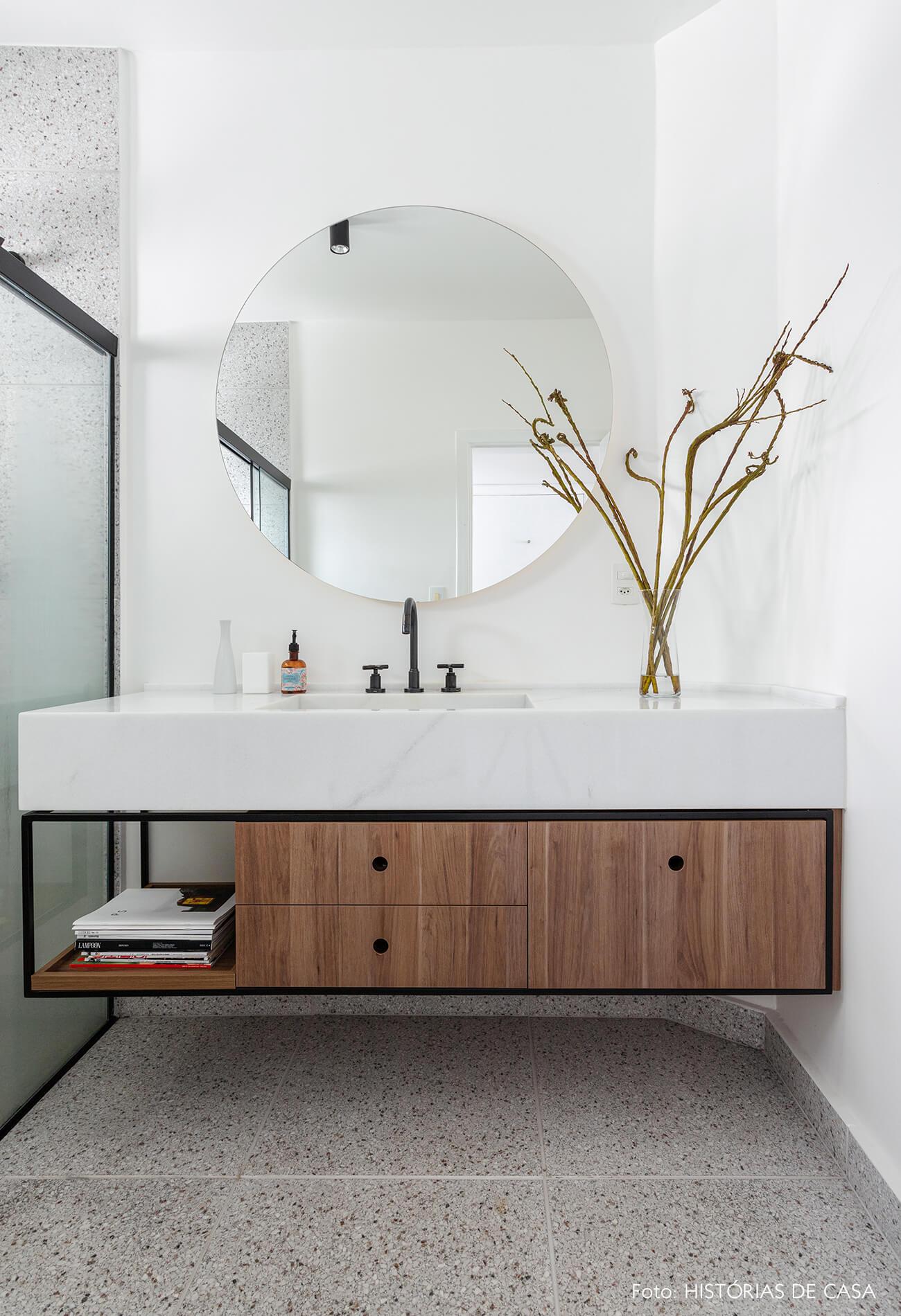 Apartamento escandinavo, banheiro com espelho redondo e tons sóbrios