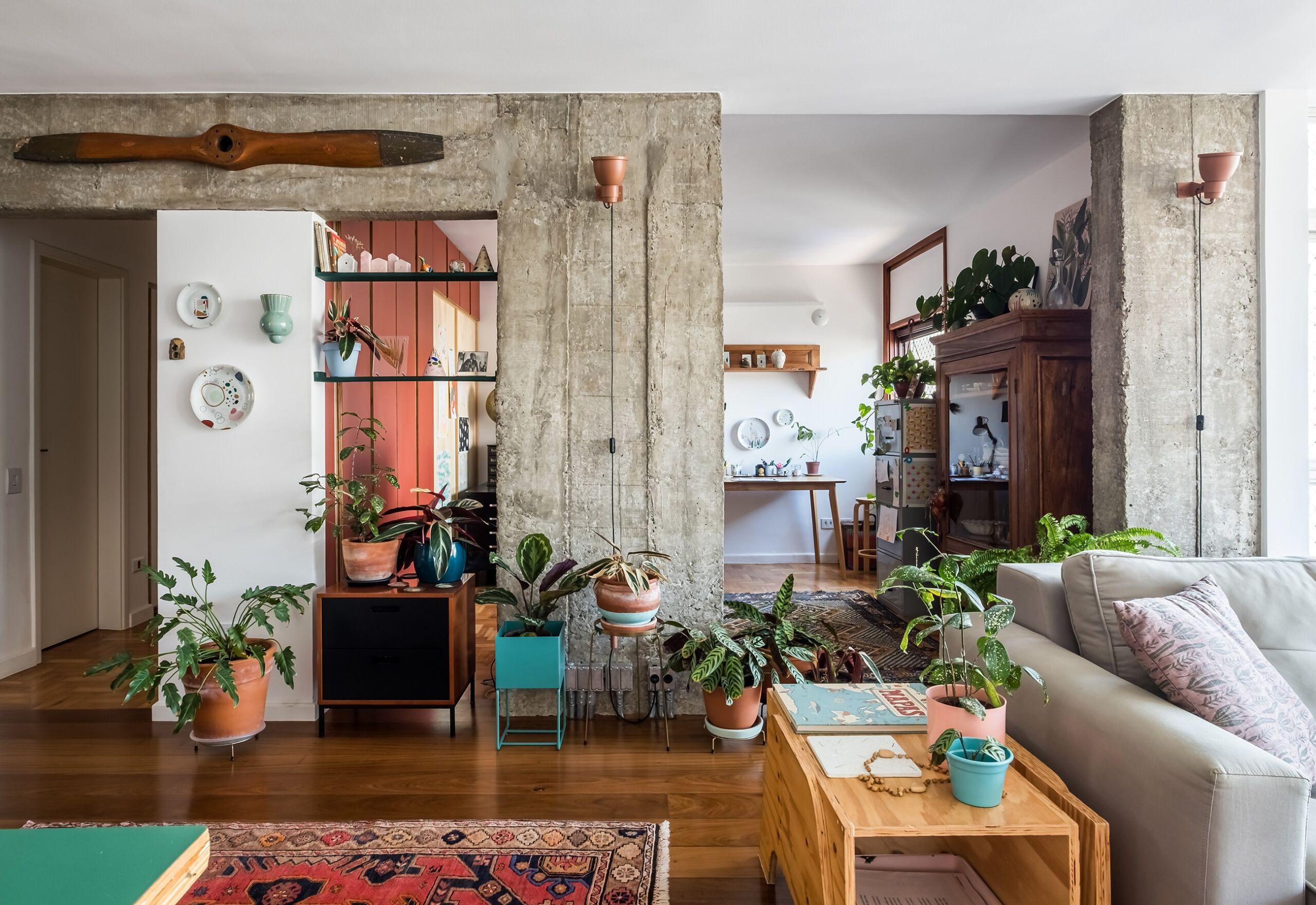 Apartamento reformado com concreto aparente e muitas plantas
