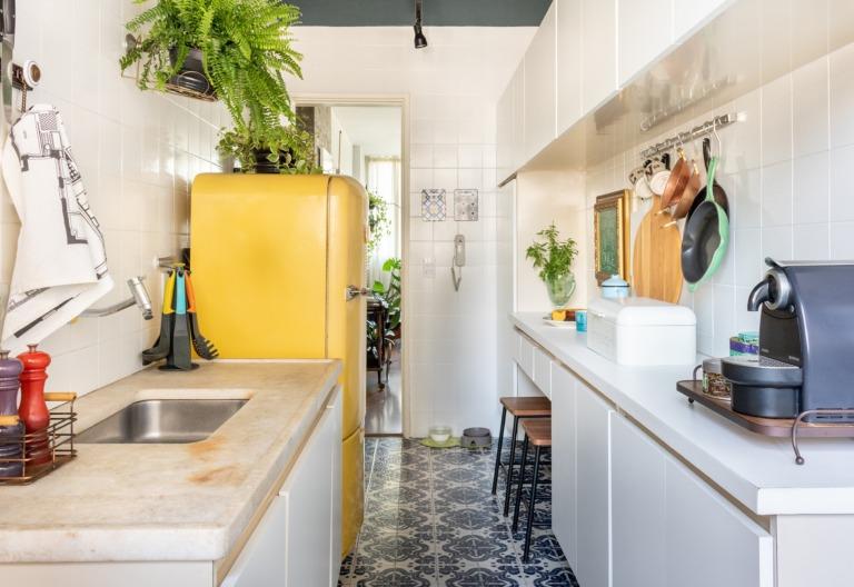 Cozinha com geladeira amarela e planta