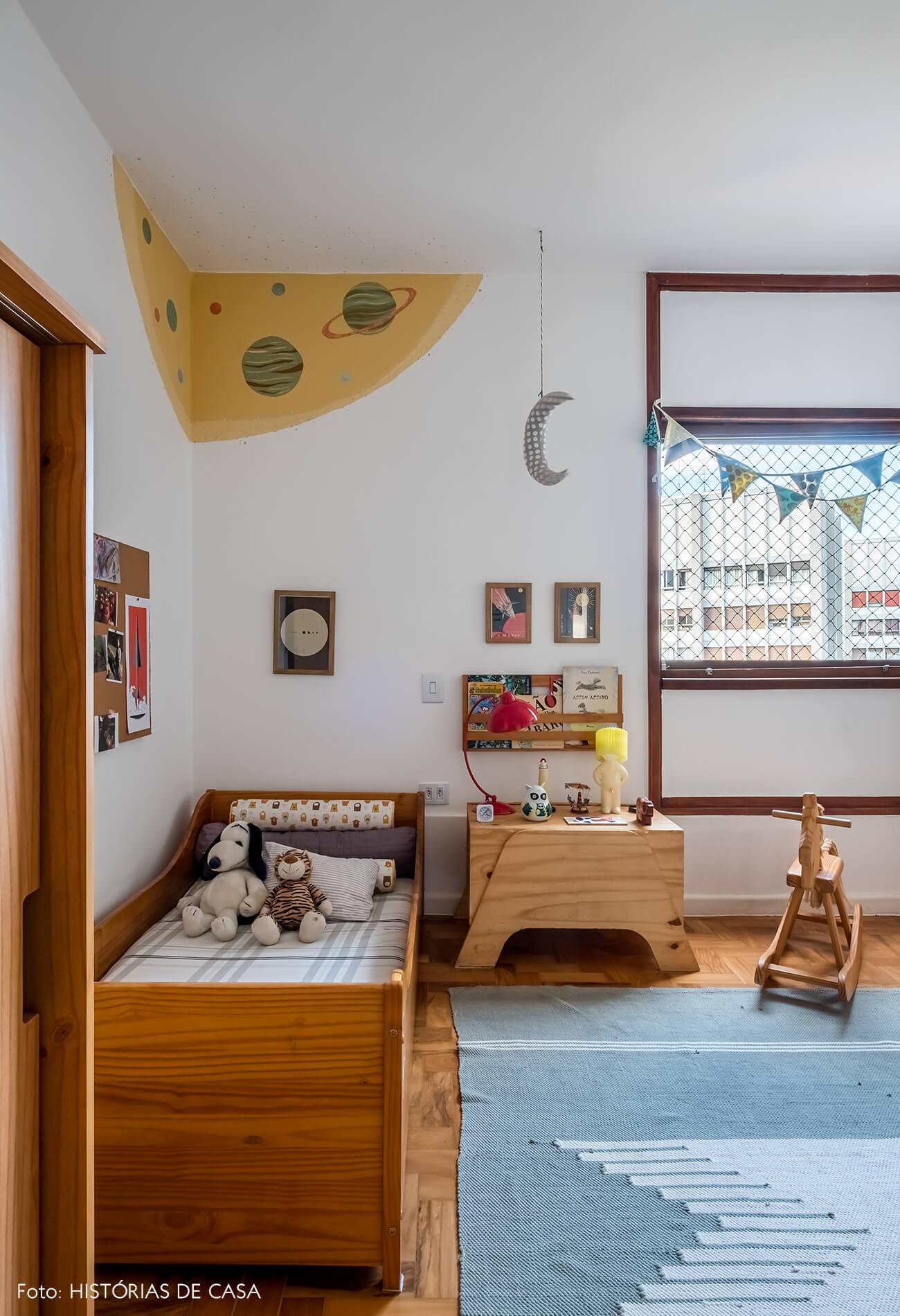Quarto de criança com móveis de madeira e pintura na parede