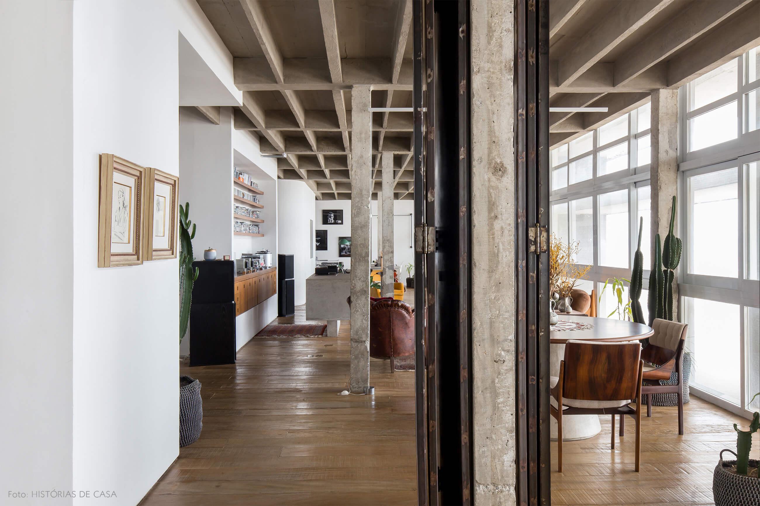 decoração colunas de concreto piso de madeira quadros e cadeira de madeira
